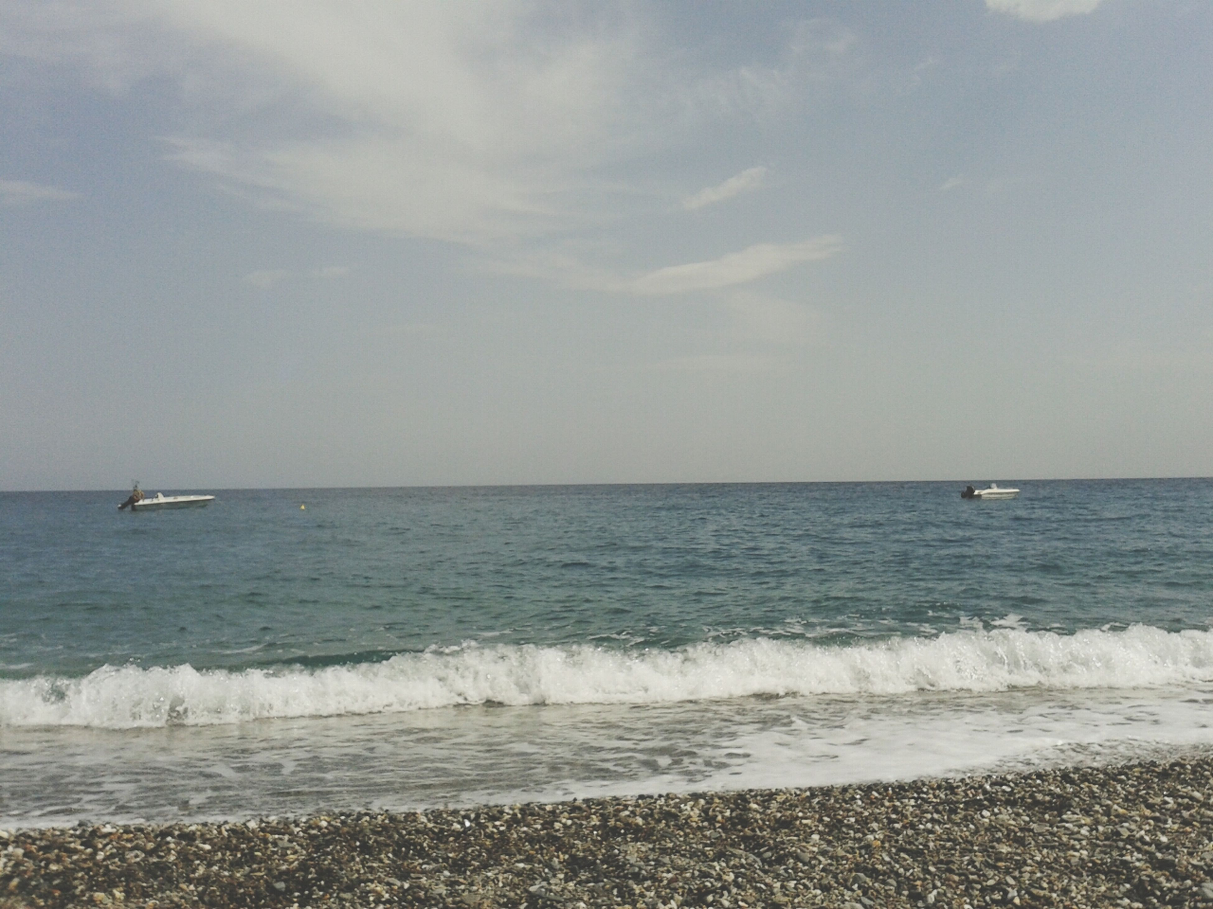 sea, horizon over water, water, nautical vessel, transportation, mode of transport, sky, boat, scenics, beach, tranquil scene, beauty in nature, shore, tranquility, nature, wave, seascape, idyllic, travel, cloud - sky