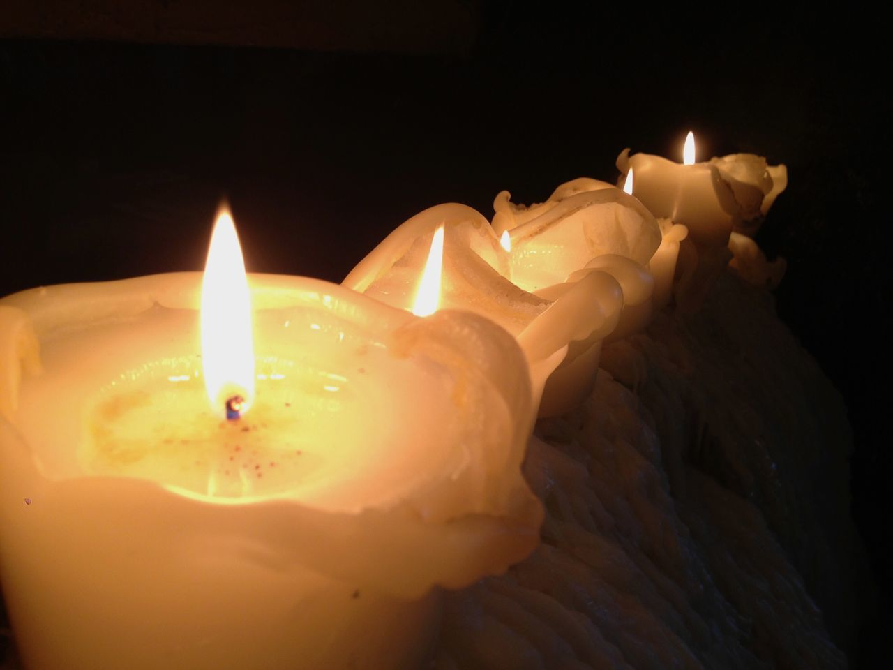 Four Candles. Candles Flames Burning Bright White Light In Dark Wax Melting Liquid