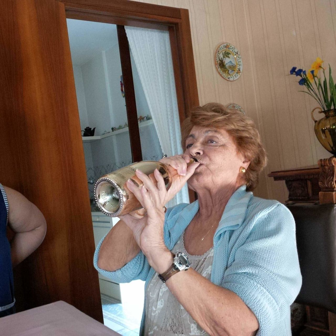 Senior Woman Drinking Wine While Sitting By Table At Home