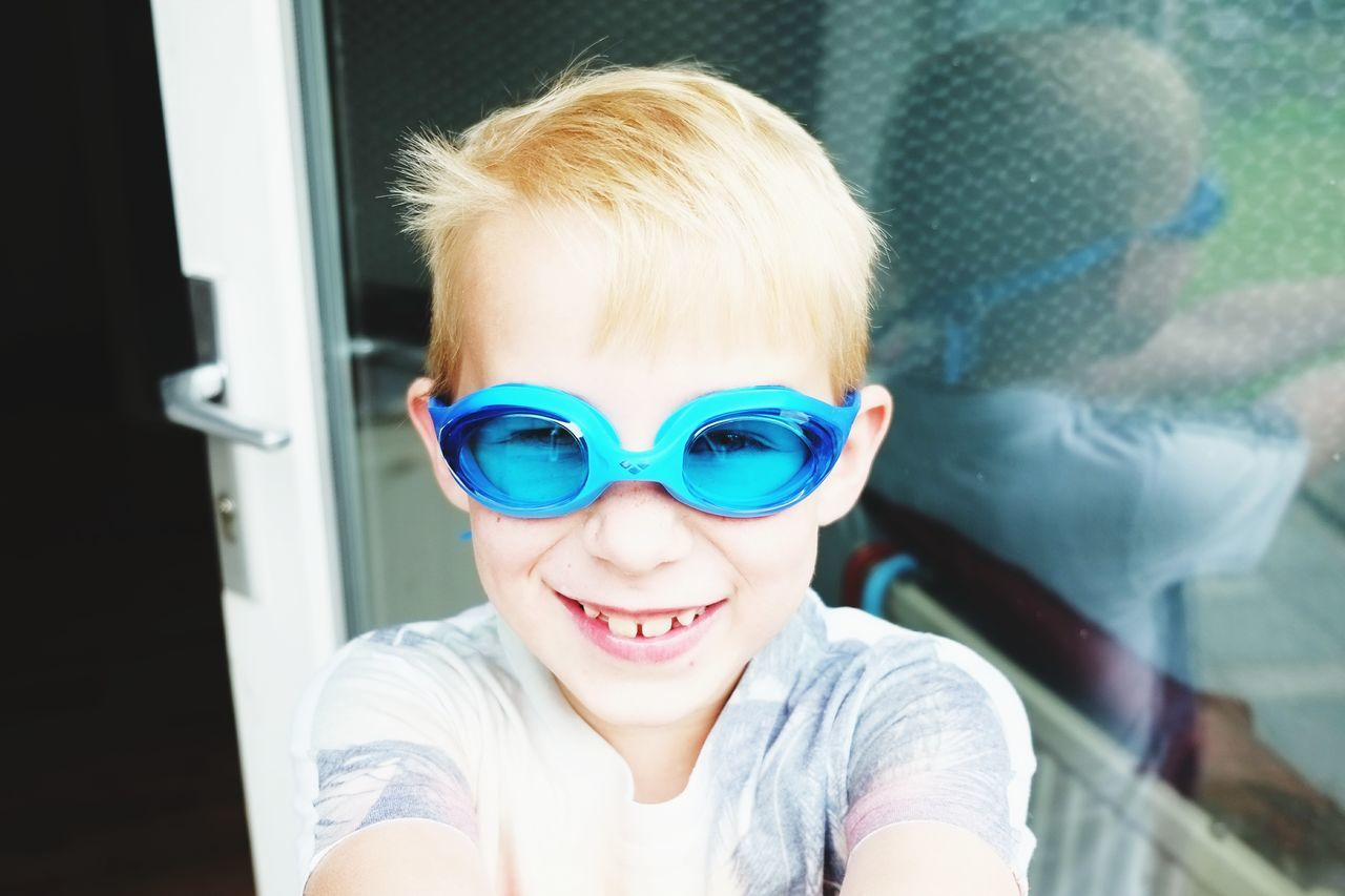 High Angle Portrait Of Cheerful Boy Wearing Swimming Goggles While Standing At Doorway