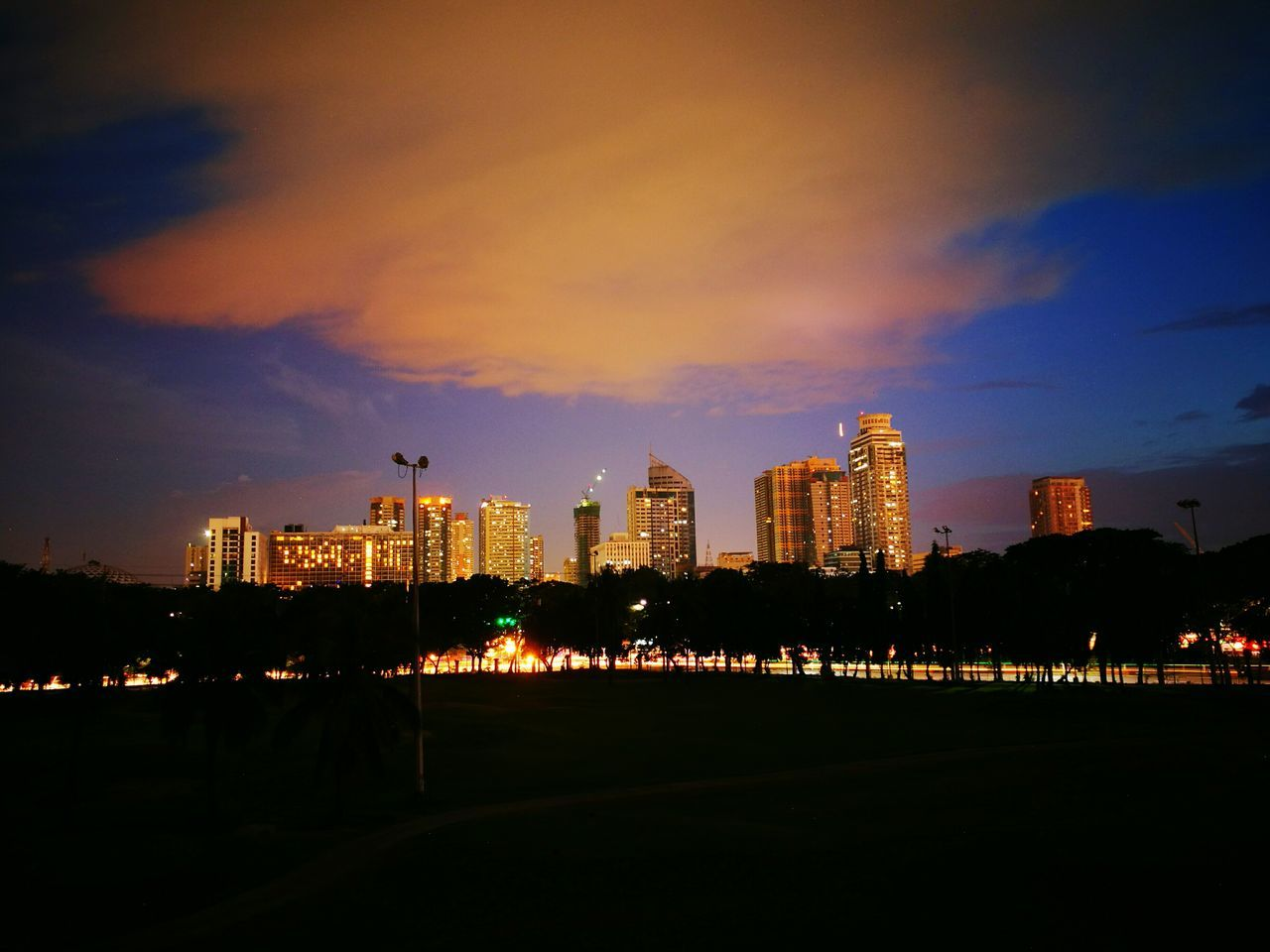 architecture, building exterior, city, skyscraper, built structure, illuminated, sky, cityscape, modern, travel destinations, no people, road, cloud - sky, urban skyline, night, outdoors