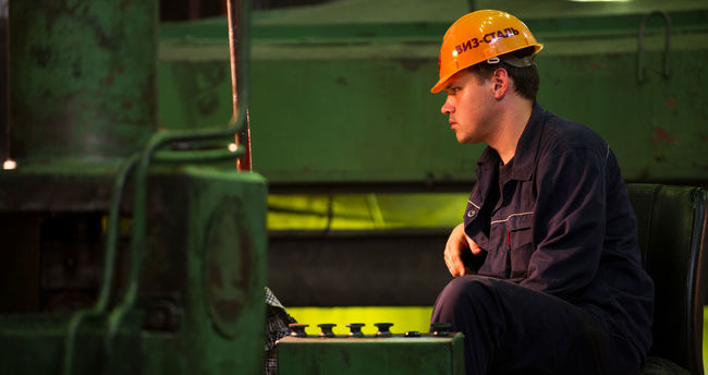 Russia, Yekaterinburg, Upper Iset plant, steel cold rolling mill Casual Clothing Contemplation Focus On Foreground Illuminated Jacket Leisure Activity Lifestyles Looking Away Russia, Yekaterinburg, Upper Iset Plant, Steel Cold Rolling Mill Sitting