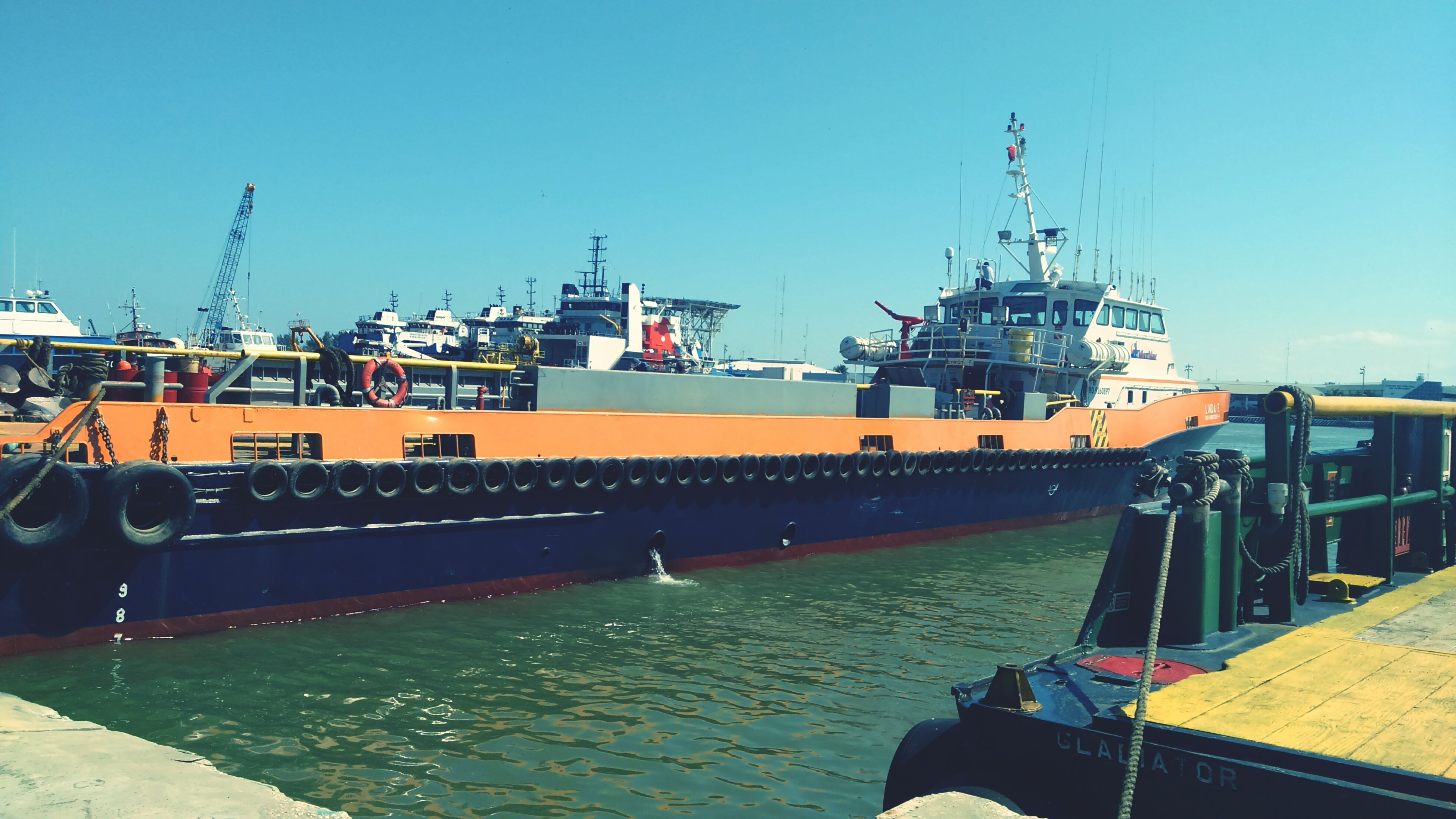 transportation, nautical vessel, clear sky, mode of transport, water, built structure, boat, harbor, moored, architecture, crane - construction machinery, building exterior, commercial dock, copy space, industry, freight transportation, mast, blue, ship, river