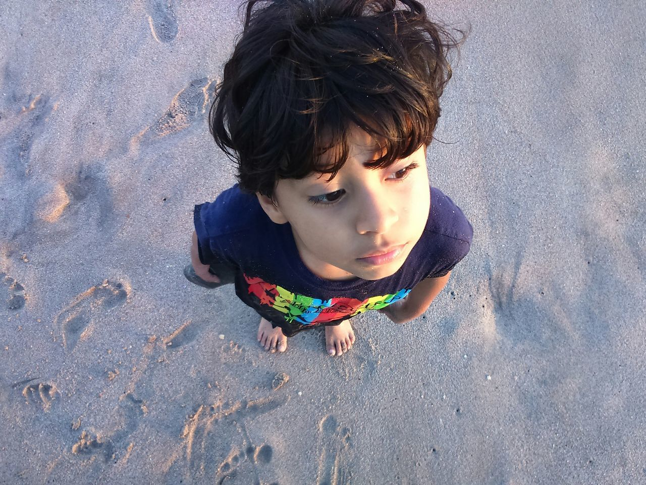 sand, high angle view, childhood, beach, one person, leisure activity, boys, outdoors, day, real people, shadow, casual clothing, elementary age, sunlight, lifestyles, multi colored, sand pail and shovel, one boy only, people