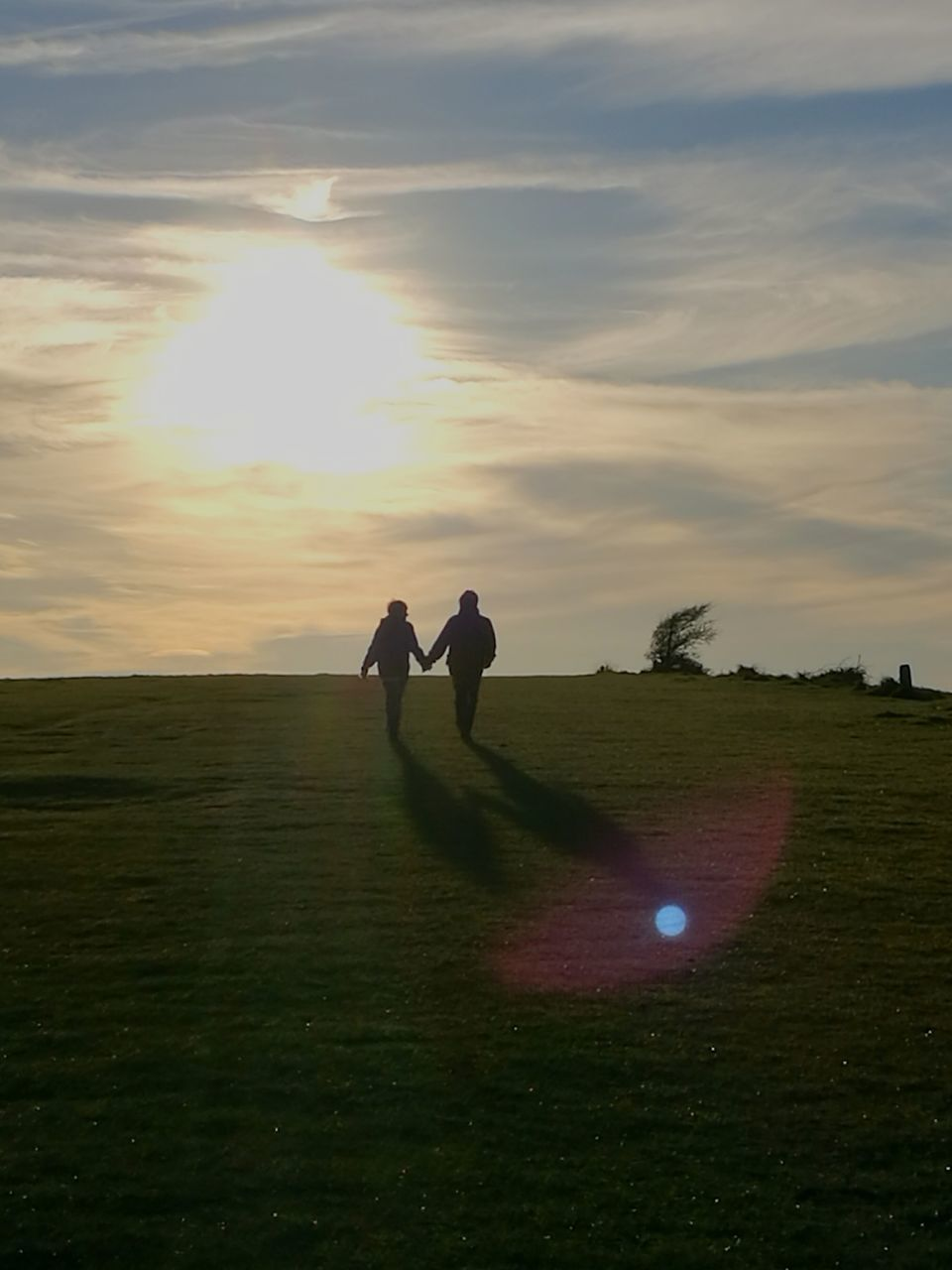 two people, real people, field, sunset, grass, leisure activity, nature, togetherness, men, landscape, sunlight, beauty in nature, sky, tranquility, scenics, lifestyles, golf course, full length, outdoors, golf, day, golfer, people
