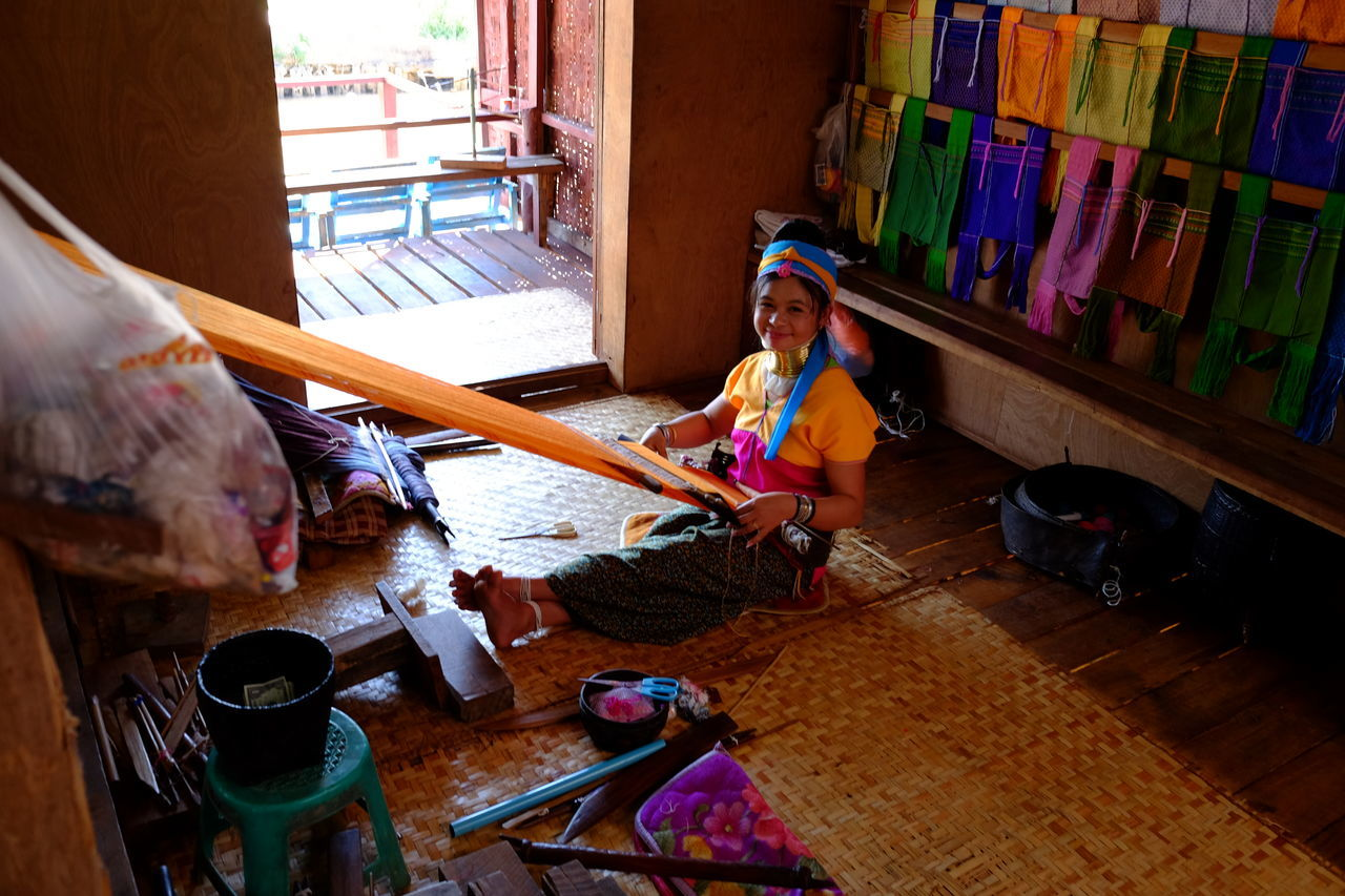 Kayan Tribes Woman Weaving Composition Domestic Life Full Frame Full Length Happy High Angle View Indoor Photography Indoors  Inle Lake Kayan Looking At Camera Making A Living Myanmar One Woman Only Outdoors Shan State Smiling Smiling Face Sunlight And Shade Tourism Tribal Art Tribal Clothing Tribal Culture Weaving Young Women