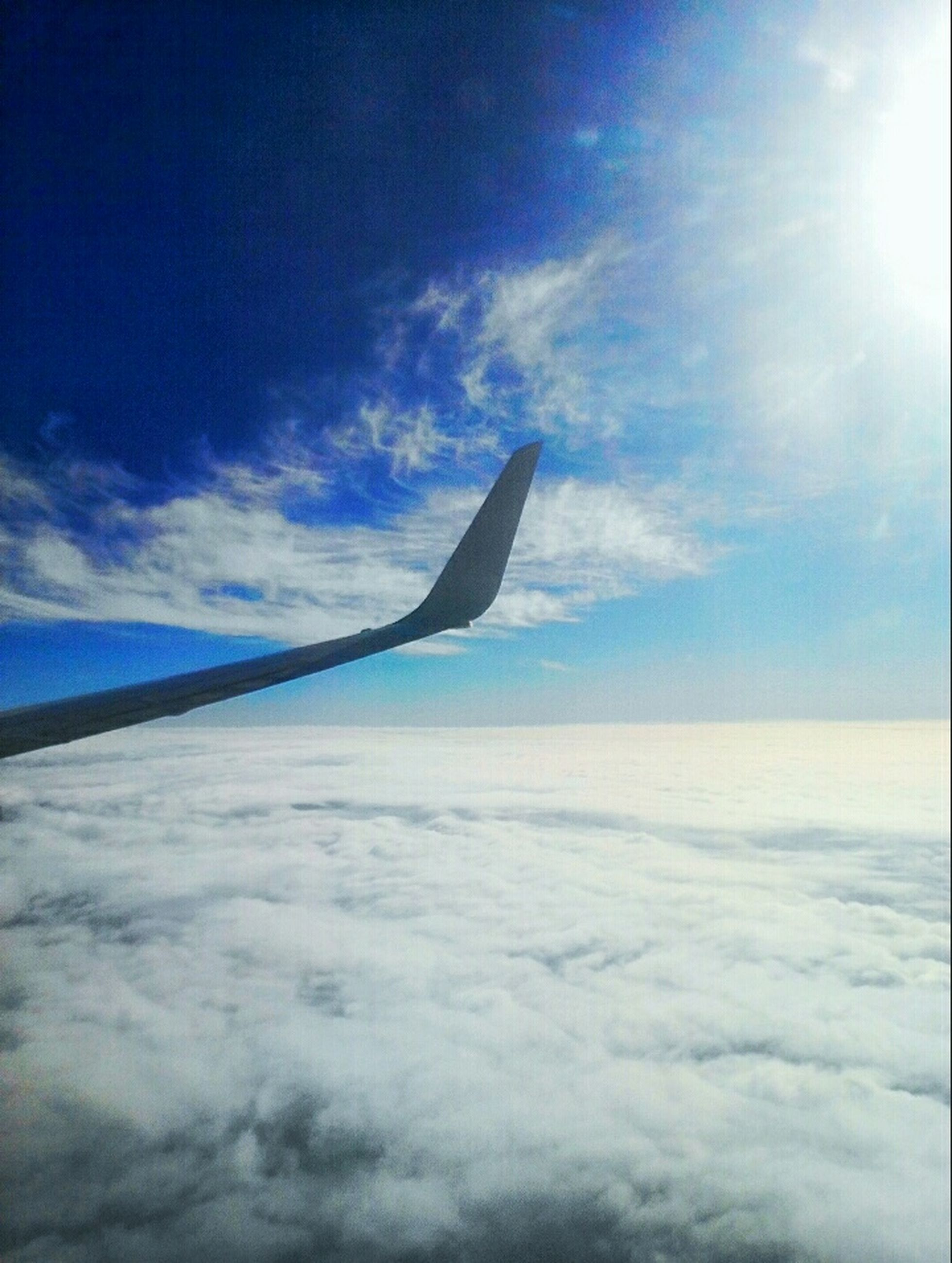 flying, airplane, sky, transportation, air vehicle, aircraft wing, blue, mode of transport, mid-air, cloud - sky, beauty in nature, part of, nature, sea, scenics, travel, cloud, cropped, on the move, tranquil scene