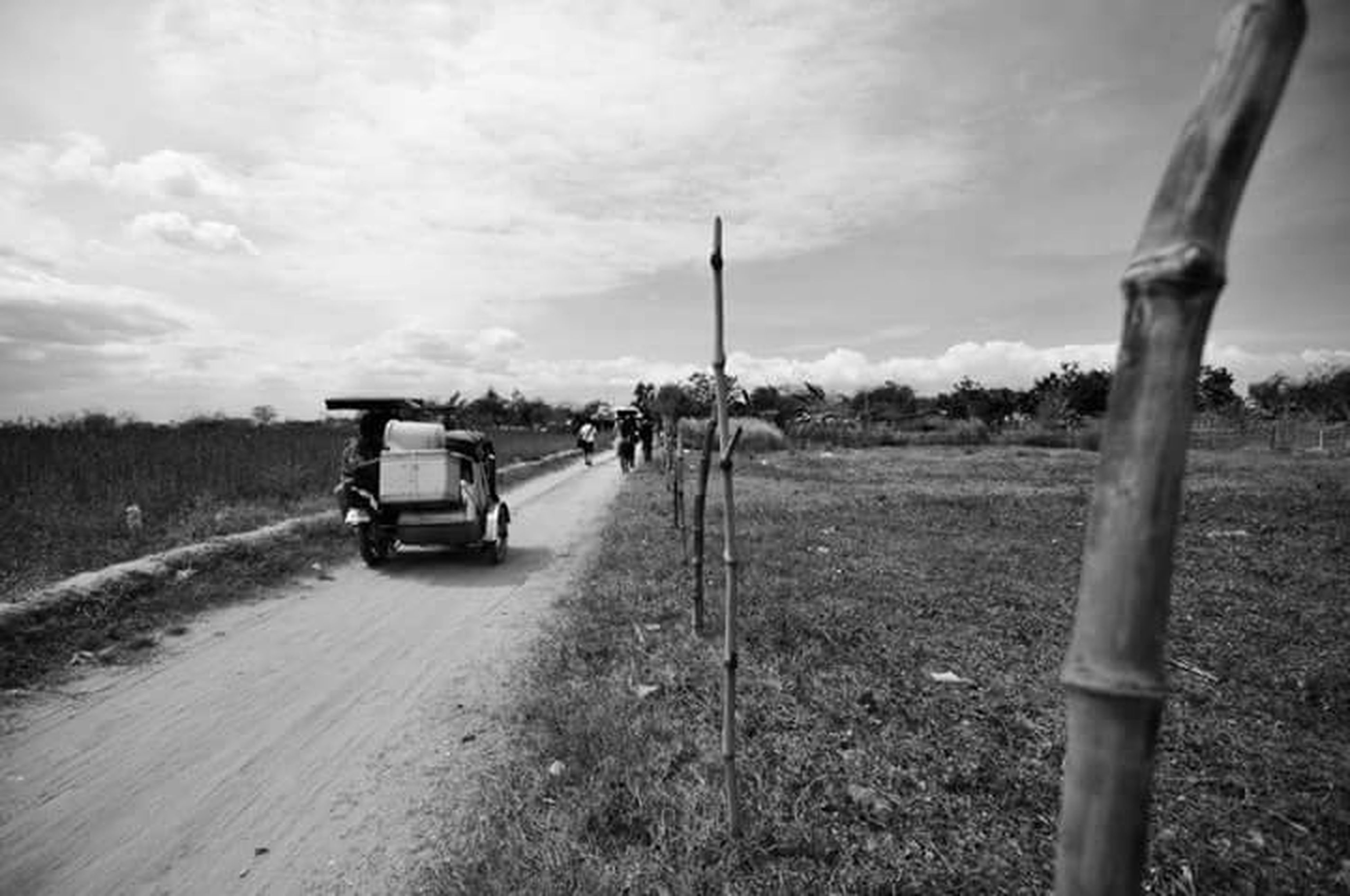 transportation, land vehicle, sky, mode of transport, road, cloud - sky, bicycle, car, men, grass, landscape, on the move, field, riding, the way forward, cloud, dirt road, country road