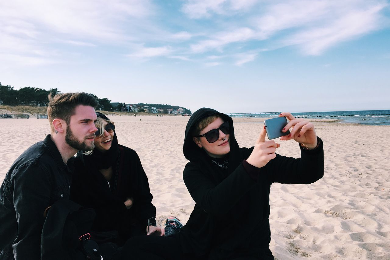 Young Friends Taking Selfie At Beach Against Sky