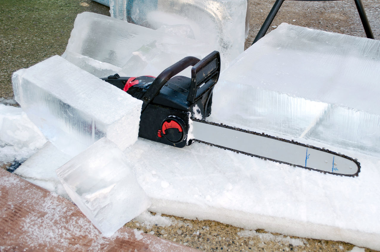 a chain saw sits on blocks of ice at an outdoor ice sculpting competition in Michigan USA Creating Art... Ice Sculpting Blade Carving - Craft Product Chain Saw Cold Competition Fragile Nature Frozen Water Hobby Ice Blocks Outdoors Tool