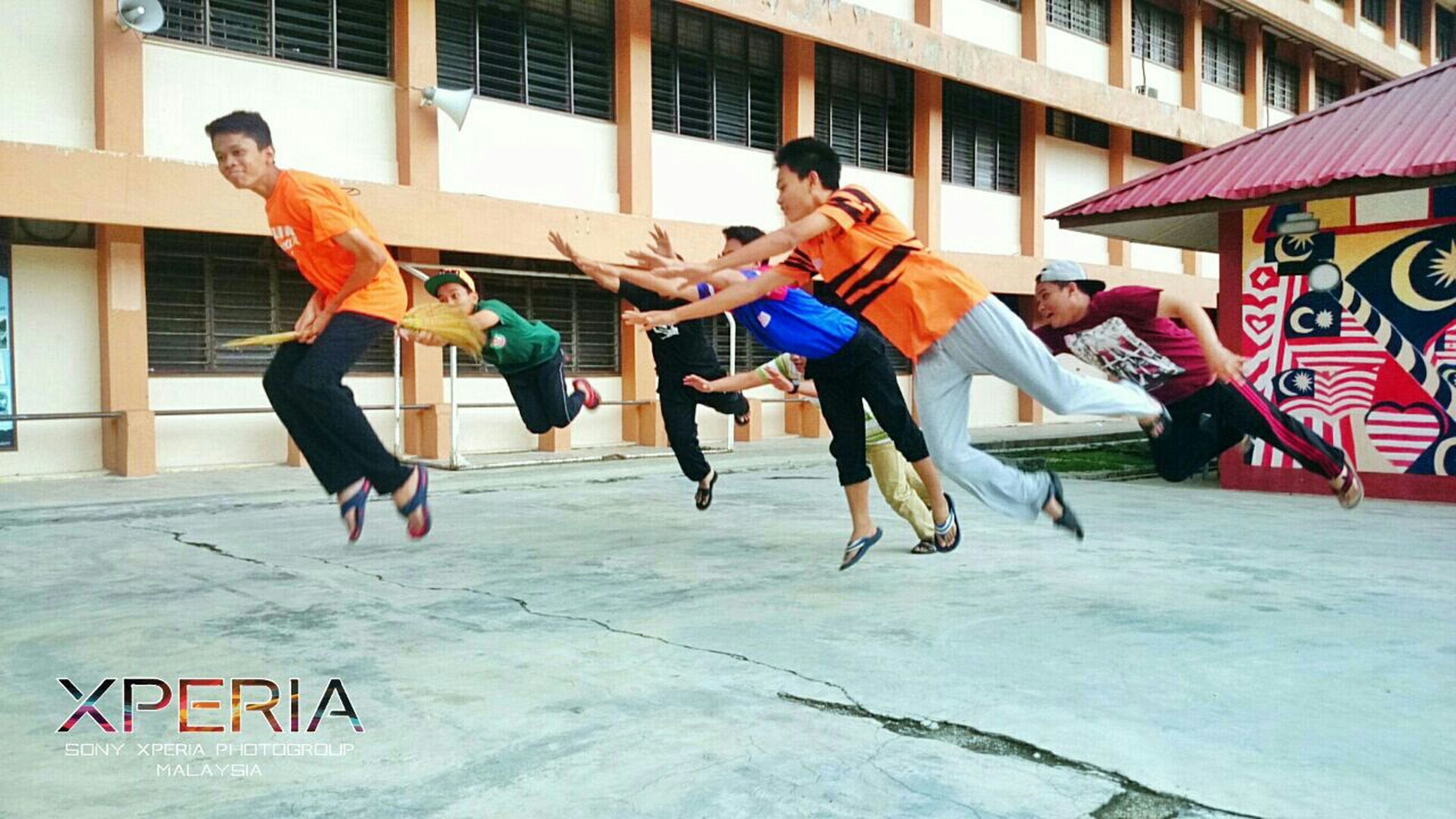 full length, lifestyles, leisure activity, building exterior, built structure, architecture, jumping, mid-air, casual clothing, happiness, men, fun, person, enjoyment, togetherness, skill, motion, young adult
