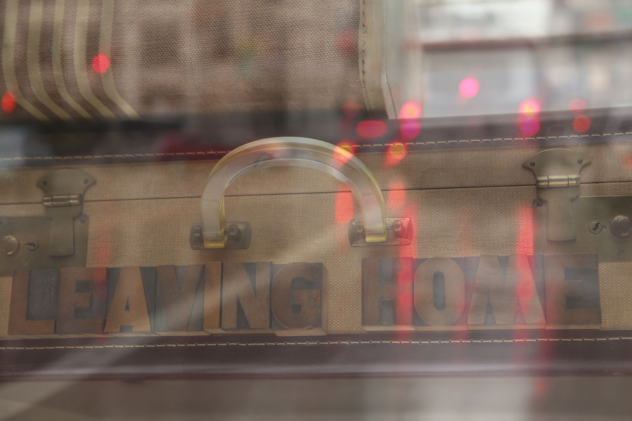 The words leaving home on a vintage suitcase layered with an image of traffic on a rainy day Alienation Brake Lights Cars Concept Defocused Departing Illuminated Leaving Home Letters Loneliness Luggage Memory No People Nostalgia Photo Composite Retro Selective Focus Suitcases Traffic Transprtation Typography Urban Vintage Words
