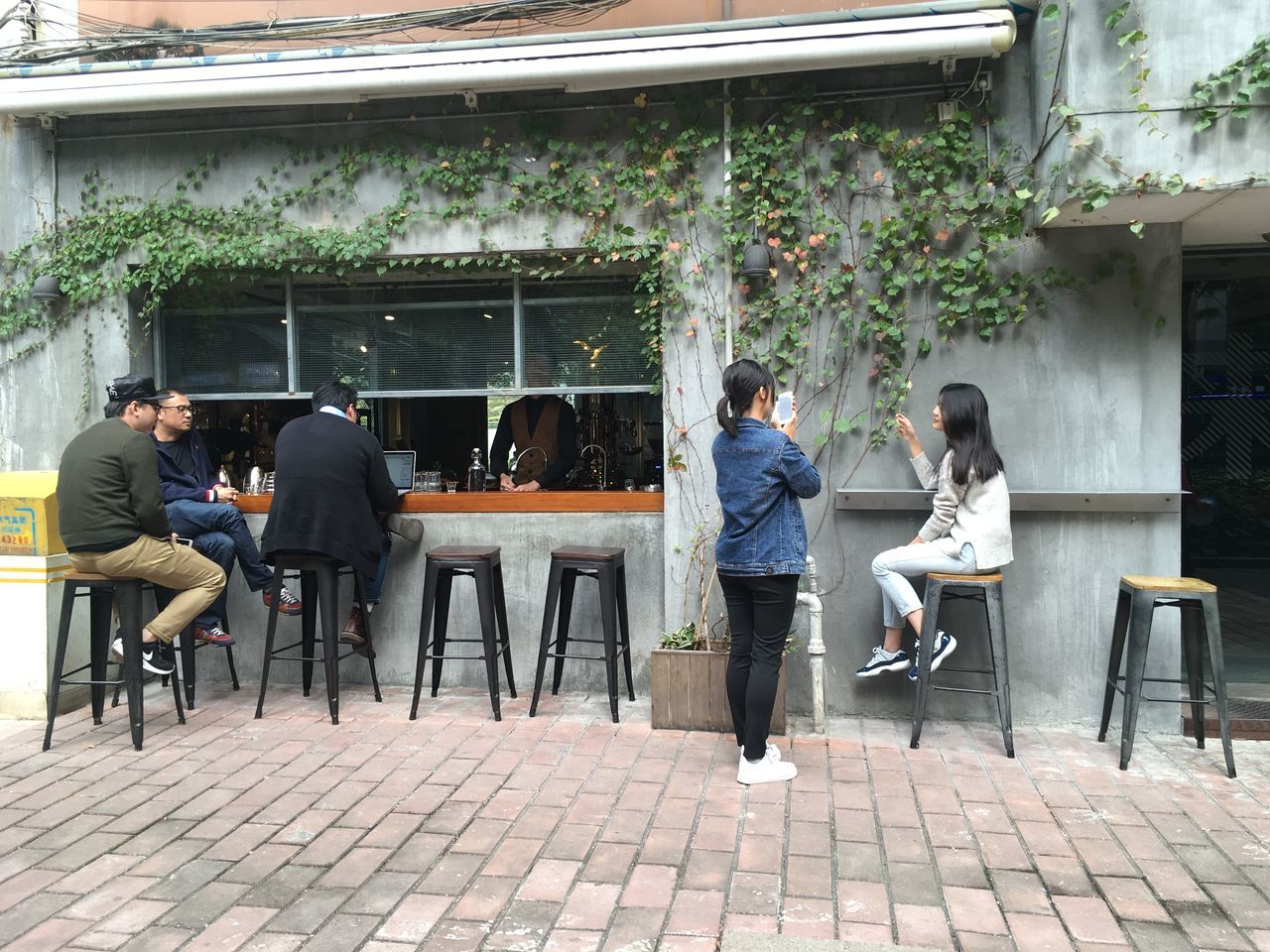 chair, full length, real people, casual clothing, table, day, sidewalk cafe, restaurant, sitting, outdoors, men, togetherness, cafe, lifestyles, women, leisure activity, tree, standing, building exterior, young adult, young women, friendship, architecture, adult, people