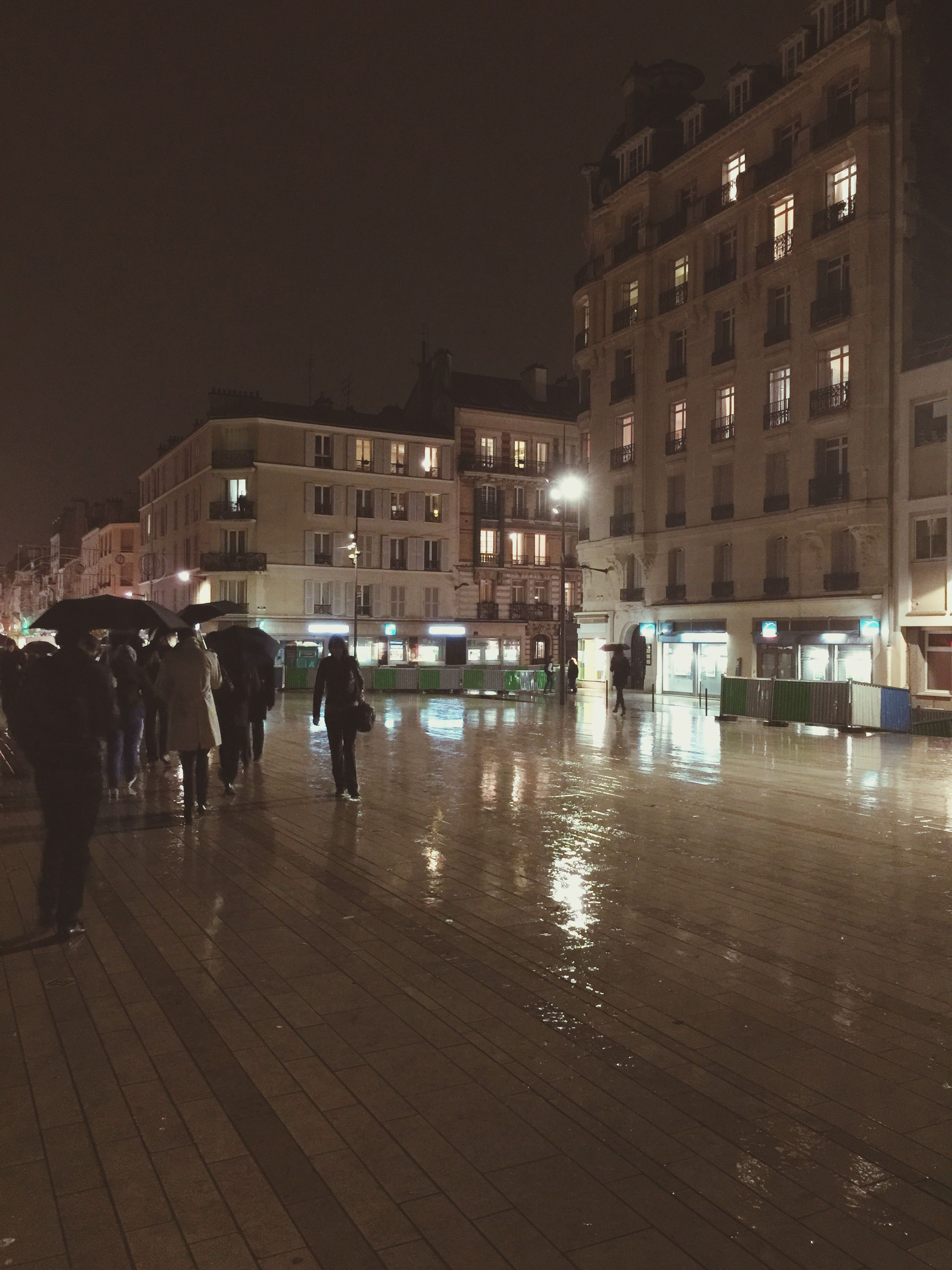 building exterior, architecture, night, built structure, city, illuminated, men, street, walking, city life, lifestyles, person, building, leisure activity, large group of people, full length, city street, street light, outdoors