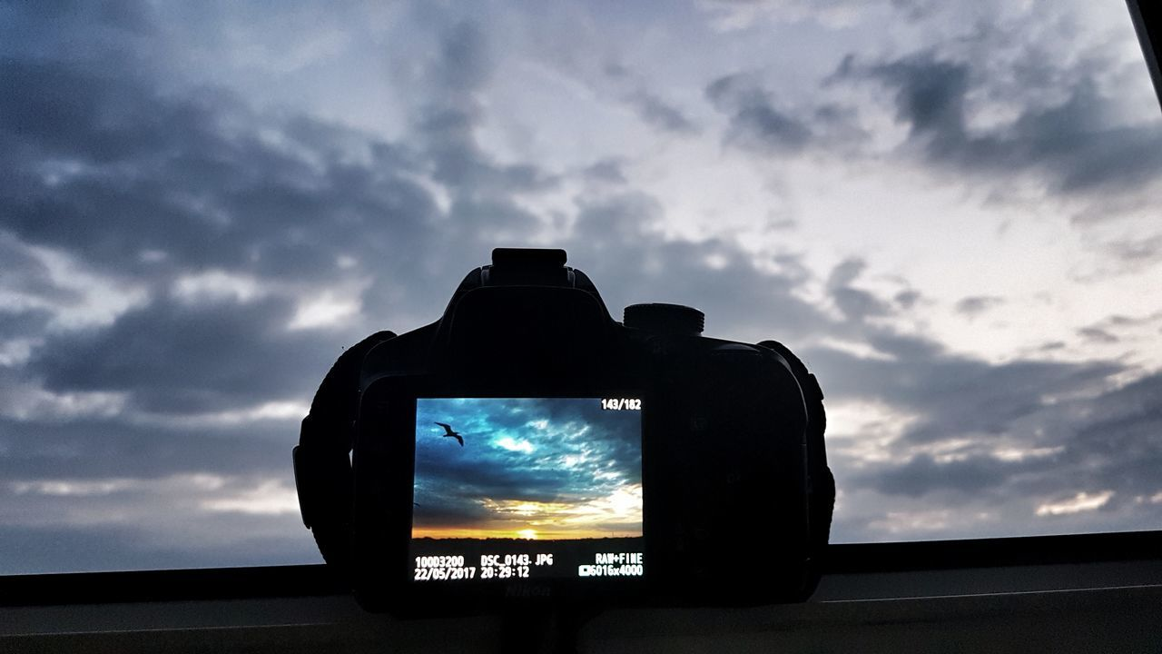 photography themes, photographing, camera - photographic equipment, technology, sky, cloud - sky, communication, silhouette, digital camera, wireless technology, device screen, low angle view, no people, sunset, outdoors, day, modern, nature, close-up, digital single-lens reflex camera