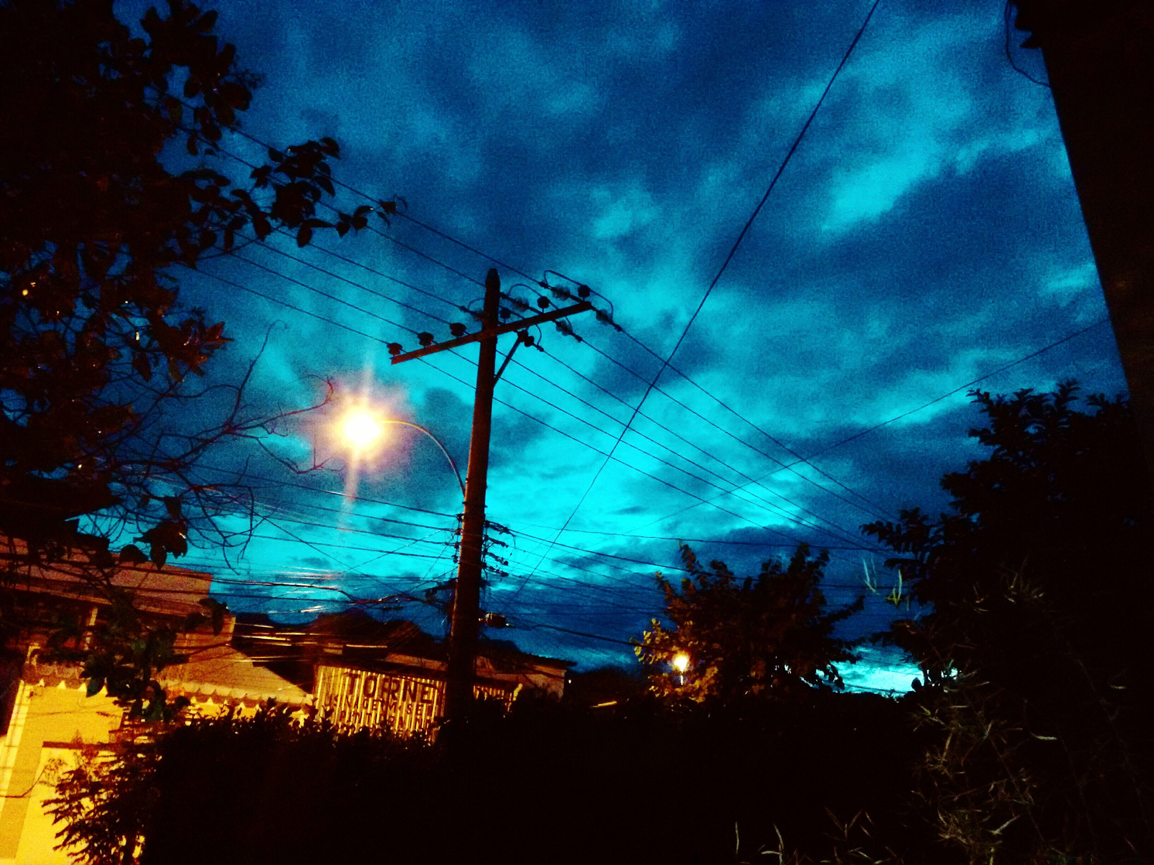 sky, low angle view, silhouette, tree, power line, cloud - sky, electricity, electricity pylon, sun, sunset, fuel and power generation, beauty in nature, nature, power supply, tranquility, scenics, cloudy, cloud, vapor trail, sunbeam