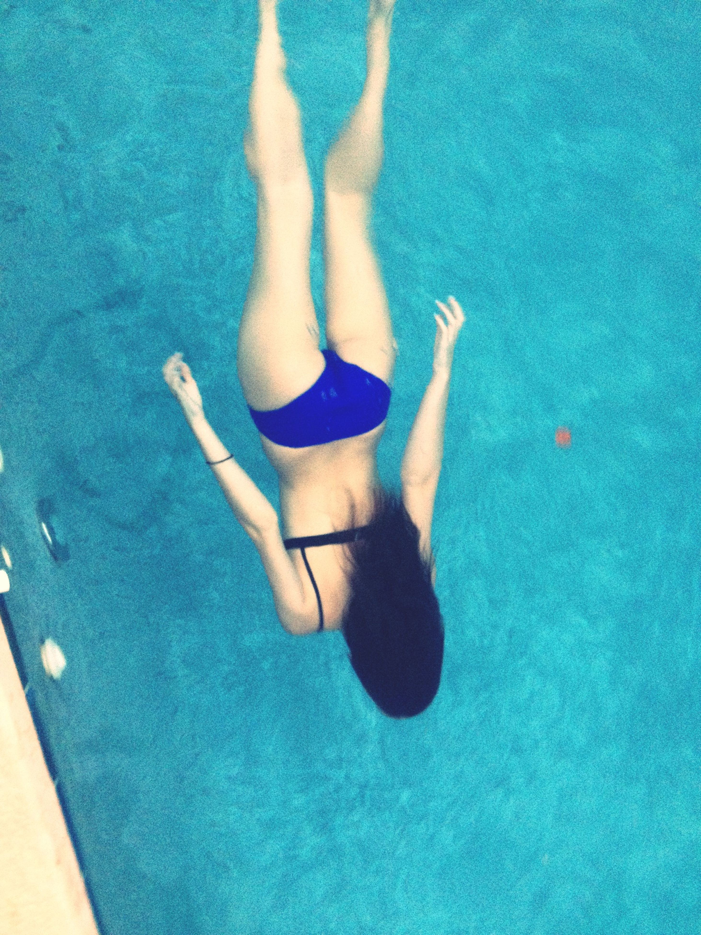 lifestyles, leisure activity, low section, person, swimming pool, blue, high angle view, barefoot, water, human foot, bikini, shadow, young adult, enjoyment, young women, vacations