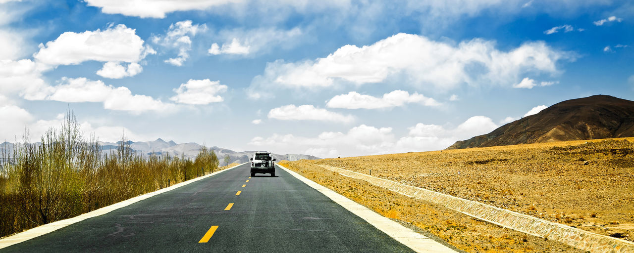 Long asphalt road in desert with blue and white sky . Cloud - Sky Day Dividing Line Driving Highway Landscape Mountain No People Outdoors Road Road Marking Sky The Way Forward Transportation Winding Road