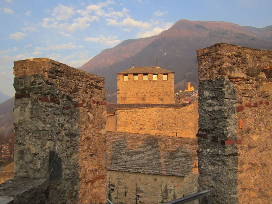 Bellinzona is home to three of the best-preserved medieval castles in Switzerland (Castelgrande, Montebello, and Sasso Corbaro); UNESCO World Heritage Sites since the year 2000. The Ramparts of Bellinzona connect Castelgrande to Castello di Montebello. I was lucky with the early March weather when I climbed up on to the ramparts, just as the golden glow of the setting sun painted a beautiful picture for the handful of photographers gathered to capture the image; while a young couple gazed lovingly the other way. The Three Castles, Defensive Wall and Ramparts make a visit to the Italian canton of Ticino's capital one of the highlights on The Grand Tour of Switzerland; a city that many tourists on their way to the towns of Locarno and Ascona, on the shores of Lago Maggiore, tend to overlook. http://pics.travelnotes.org Architecture Bellinzona Blue Sky Castles Cutural Heritage Golden Golden Hour Historical Sights Medieval Michel Guntern Montebello Mountain Range Outdoors Sightseeing Stone Wall Swiss Switzerland The Great Outdoors With Adobe Ticino Tourist Attraction  Travel Travel Photography Travel Photos Travel Pics Unesco