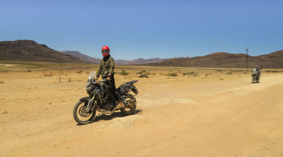 Rider standing on motorcycle along open dirt road Adventure Biker Clear Sky Desert Dirt Road Dual Sport Explore Headwear Helmet Journey Land Vehicle Landscape Leisure Activity Mode Of Transport Motorbike Motorcycle Off-road Vehicle One Person Open Road Outdoors Riding Standing Transportation Travel Destinations Let's Go. Together.