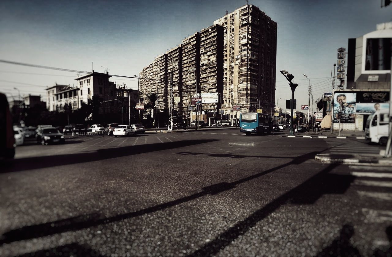 architecture, building exterior, car, transportation, built structure, city, street, road, land vehicle, city life, shadow, mode of transport, outdoors, sunlight, modern, day, skyscraper, clear sky, sky, real people