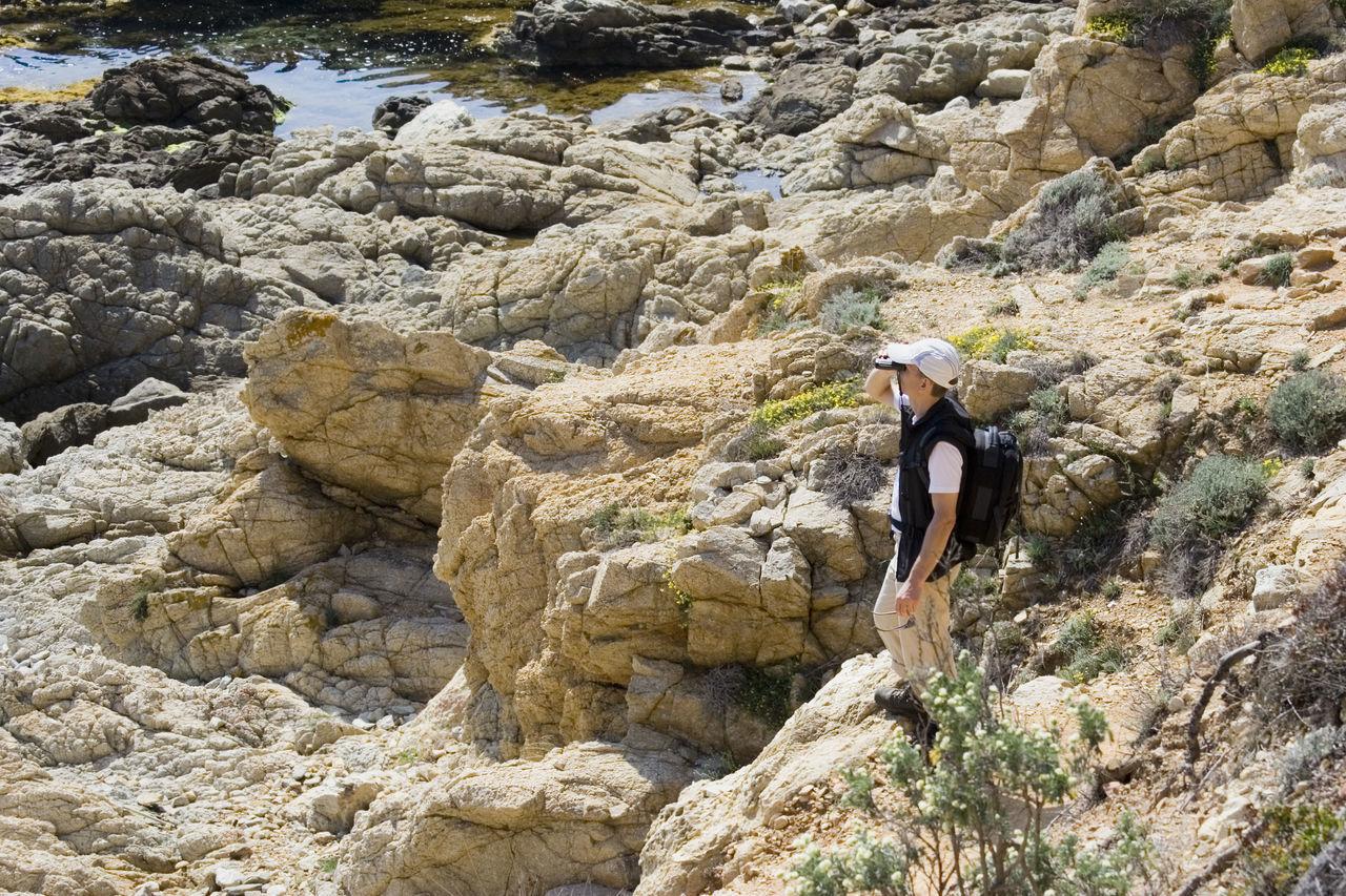 Man Hiking While Looking Through Binoculars At French Riviera