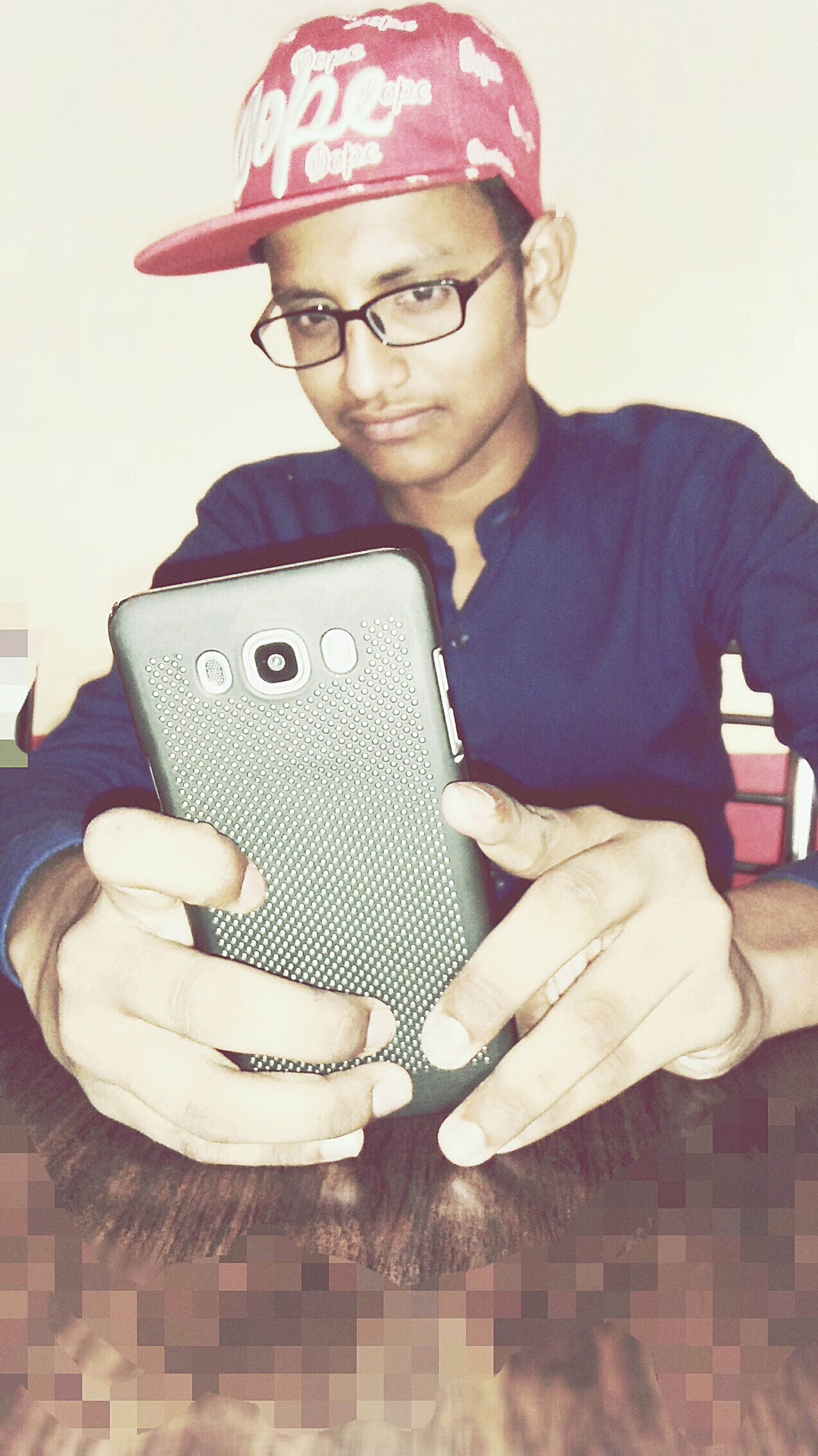 eyeglasses, one person, real people, looking at camera, cap, portrait, glasses, technology, sitting, indoors, young adult, wireless technology, day