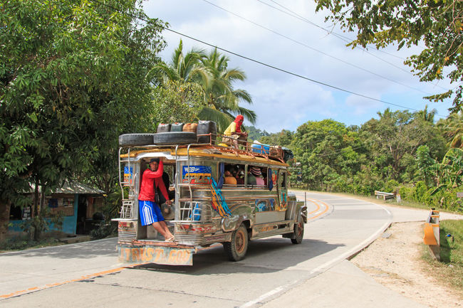Puerto Princesa, Philippines - January 12, 2015: People in colorful traditional bus jeepney in Palawan, one of the 7107 isalnds of the Philippines. Jeepney are used as a very cheap mean of transportation in the Philippines ASIA Beach Branch Cloud - Sky Corong Corong Day El Nido Land Vehicle Mode Of Transport Nacpan Outdoors Palawan Person Philippines Puerto Princesa Road Shadow Sky South East Asia Street Summer Transportation Tree Tropics Underground River
