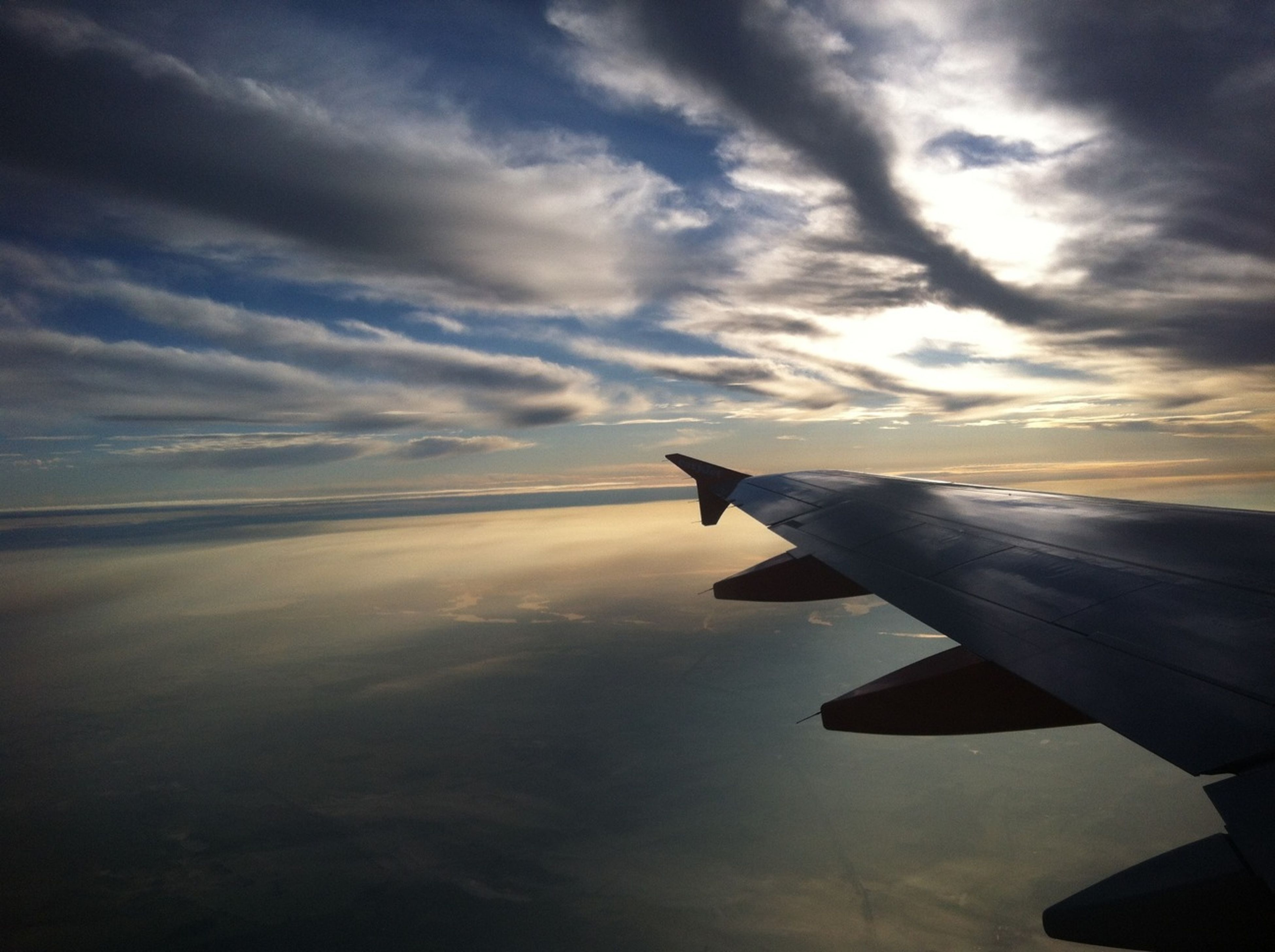 airplane, flying, sky, air vehicle, aircraft wing, sunset, cloud - sky, transportation, scenics, mid-air, beauty in nature, sea, mode of transport, part of, horizon over water, cloud, nature, travel, cropped, tranquil scene