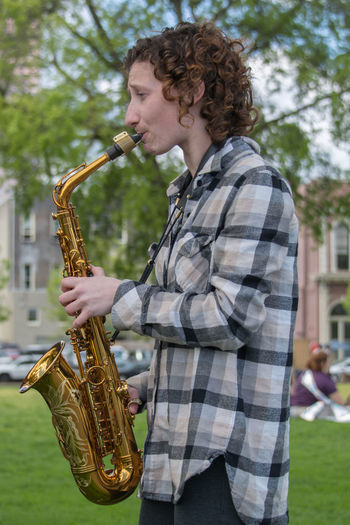 Casual Clothing Day Holding Lifestyles Music Musical Instrument Musician One Person Outdoors People Performance Playing Real People Saxophone Standing Wind Instrument Young Adult Young Women