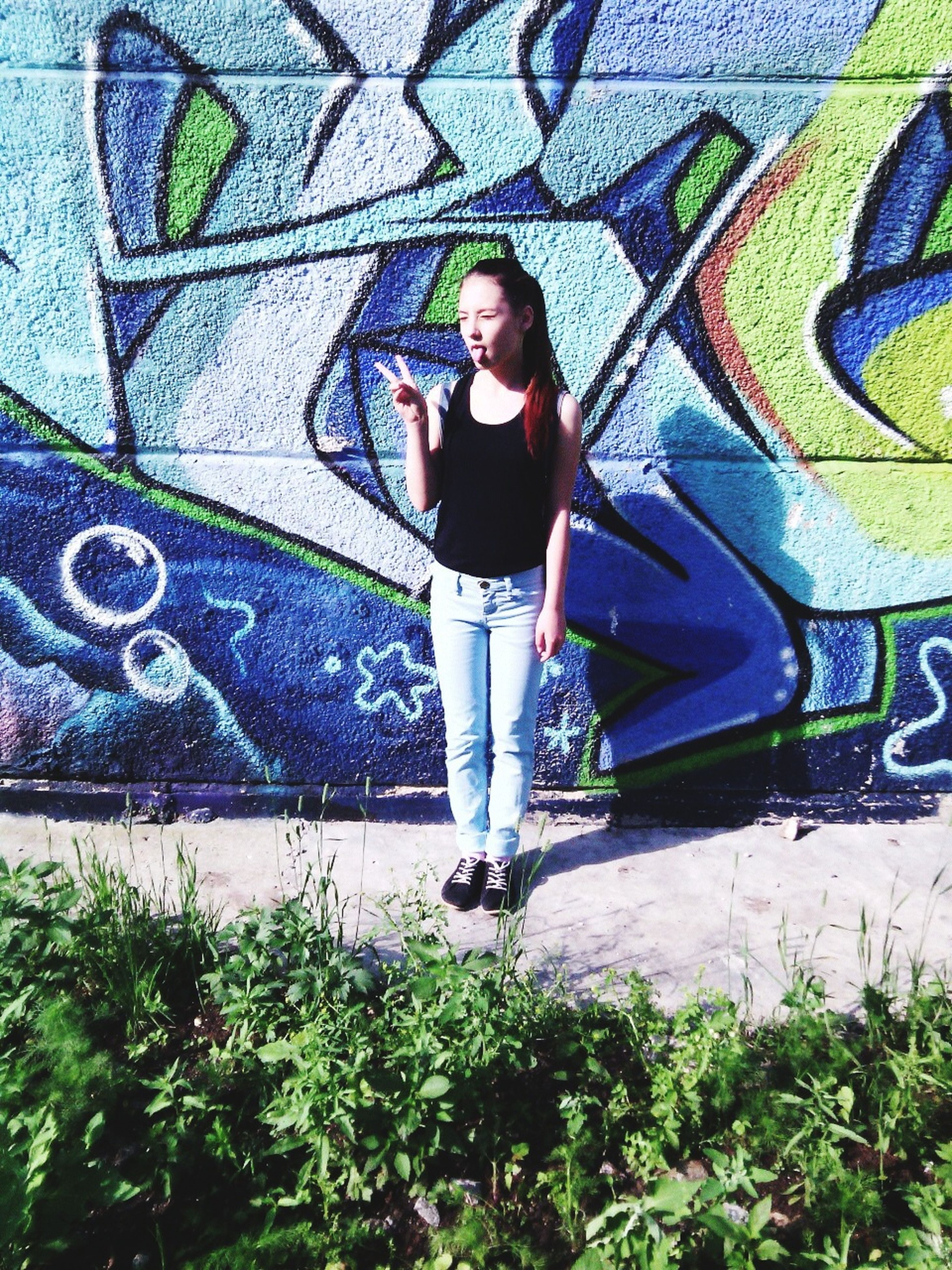 young adult, looking at camera, portrait, lifestyles, graffiti, person, casual clothing, young women, wall - building feature, front view, full length, leisure activity, standing, art, architecture, smiling, built structure