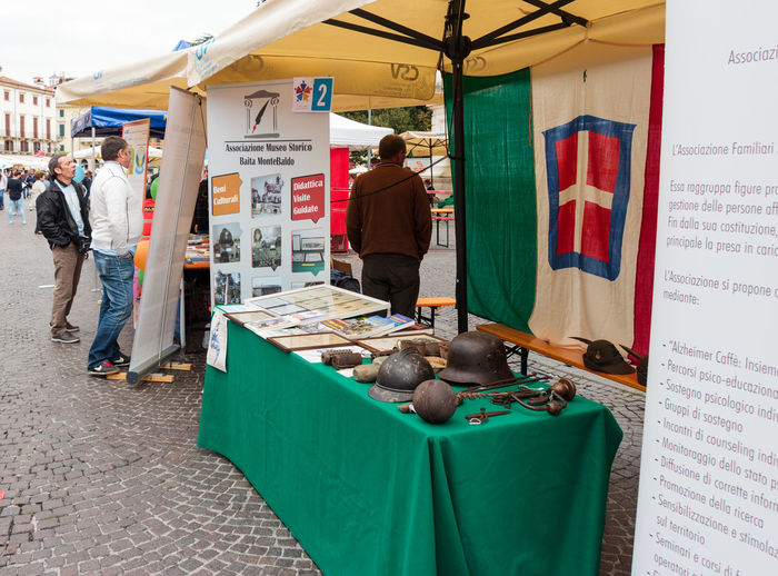 Verona, Italy, September 27, 2015 : Table with explanations and items of weapons and work tools of the Second World War during the Sunday Fair in the Piazza Bra square in Verona, Italy Adult Arms Army Buying Choice City Culture Day Equipment Europe Famous History, Italy Medieval Metal Military Old Outdoors People Place Second Store Travel Verona War