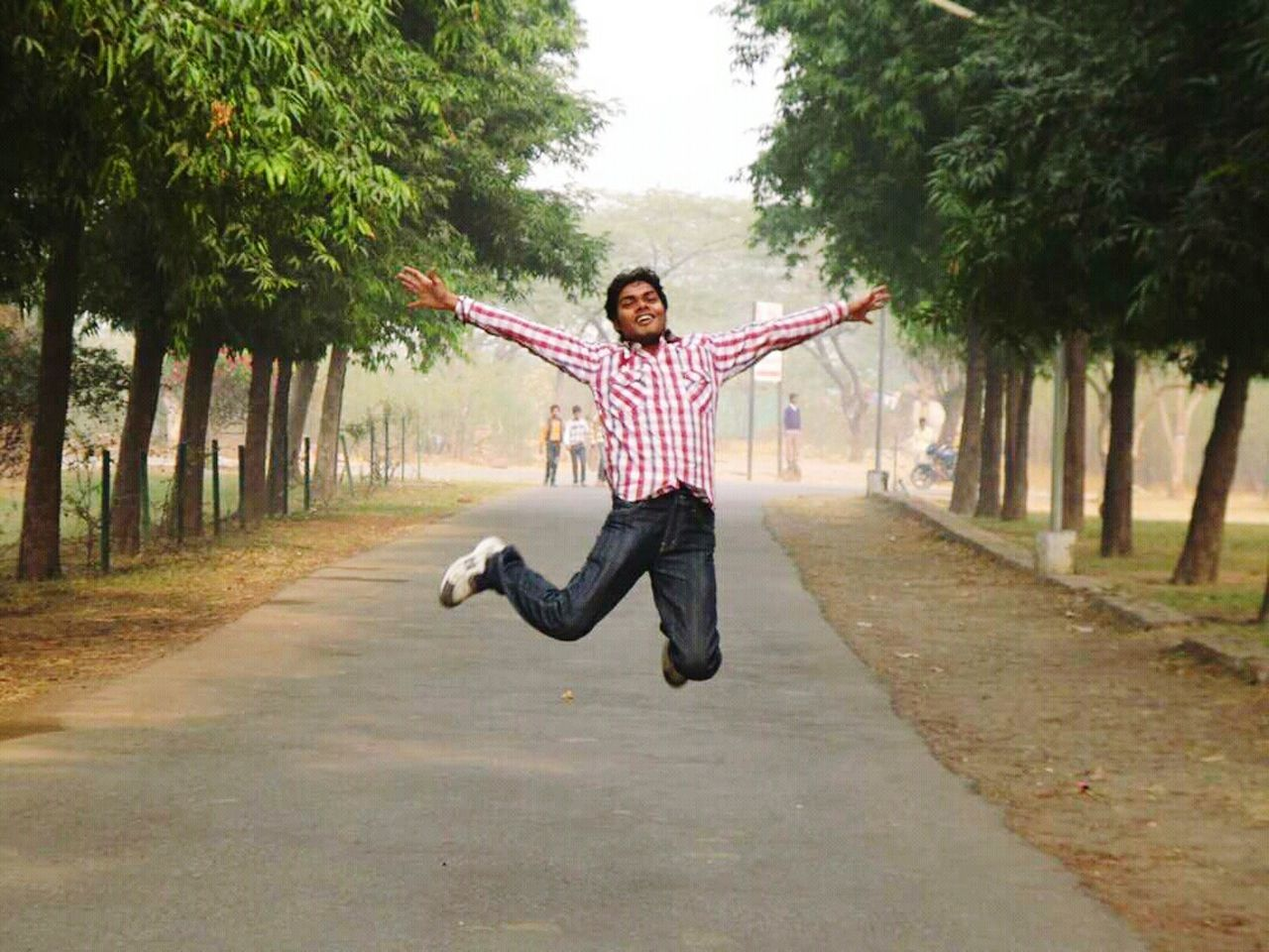 human arm, motion, one person, arms raised, tree, outdoors, casual clothing, day, full length, mid-air, human body part, jumping, arms outstretched, front view, young adult, fun, one man only, only men, men, happiness, one young man only, adult, smiling, people, adults only, nature