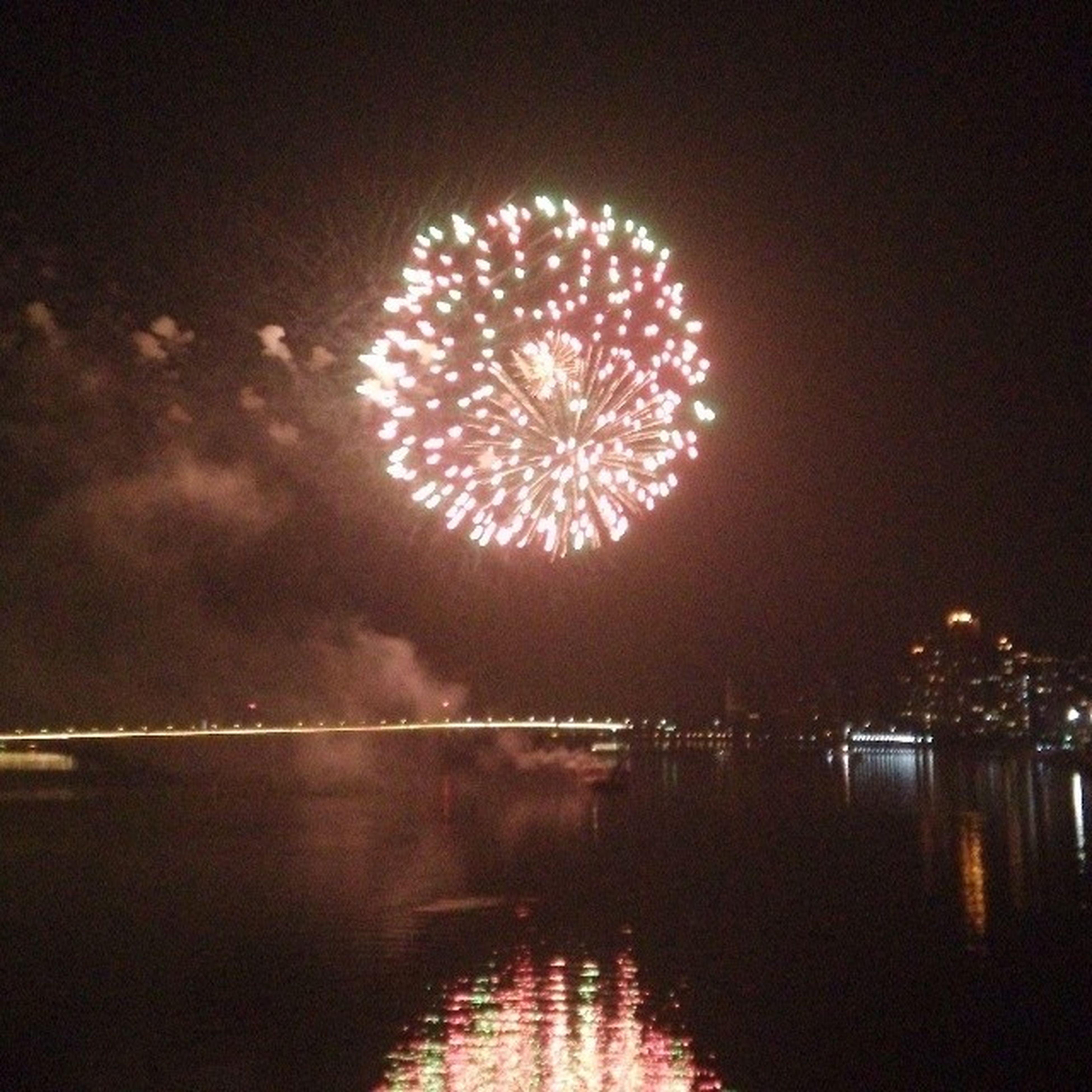 illuminated, night, water, reflection, waterfront, sky, glowing, long exposure, river, firework display, built structure, exploding, architecture, building exterior, outdoors, light, celebration, lake, arts culture and entertainment, lighting equipment
