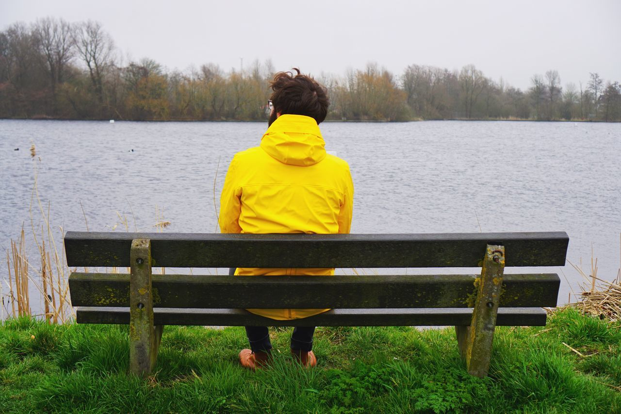 Sitting Rear View Water Full Length Nature Bench Leisure Activity Tree Real People Yellow One Person Beauty In Nature Outdoors Lake Tranquility Sky Scenics Day Growth Nature Photography Real Photography Beauty In Nature Nature Sea Waterfront