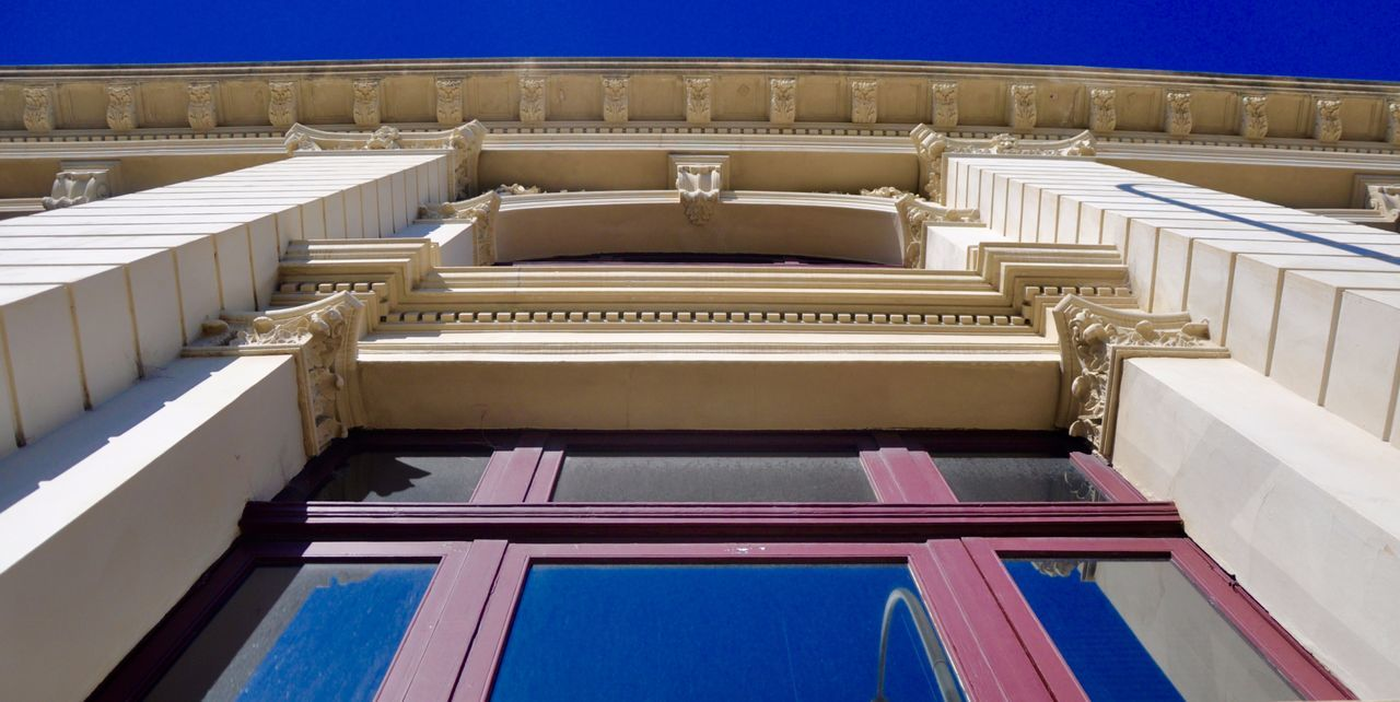 Upward perspective of building exterior with windows and architectural features in Fremantle, Western Australia. Architectural Column Architectural Feature Architecture Blue Building Building Exterior Built Structure Day Entrance Fremantle  Historic Low Angle View Moulding Outdoors Perspective Purple Sky Upward View Western Australia Window Frame Windows