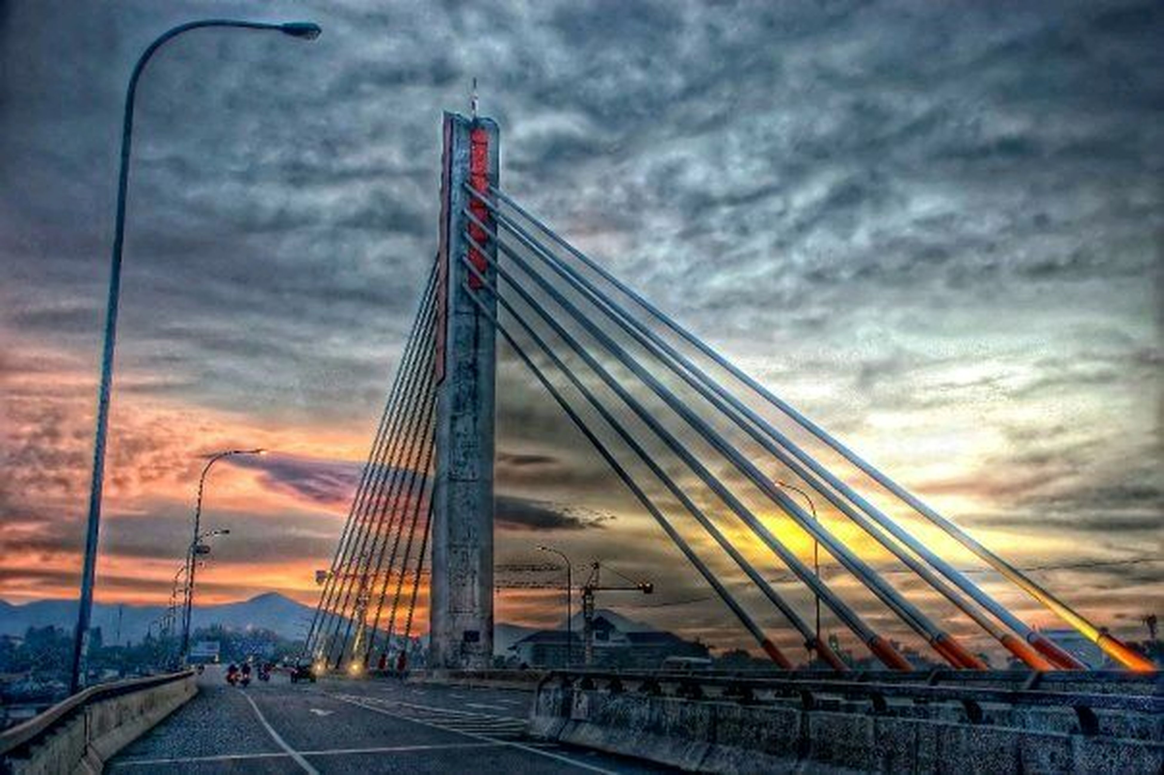 sky, cloud - sky, architecture, sunset, built structure, transportation, cloudy, cloud, connection, low angle view, bridge - man made structure, orange color, the way forward, engineering, road, outdoors, city, building exterior, street light, suspension bridge