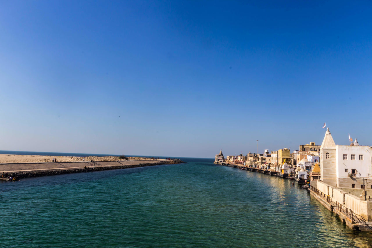 water, architecture, blue, sea, copy space, building exterior, outdoors, built structure, clear sky, sky, nature, day, waterfront, travel destinations, beauty in nature, no people, scenics