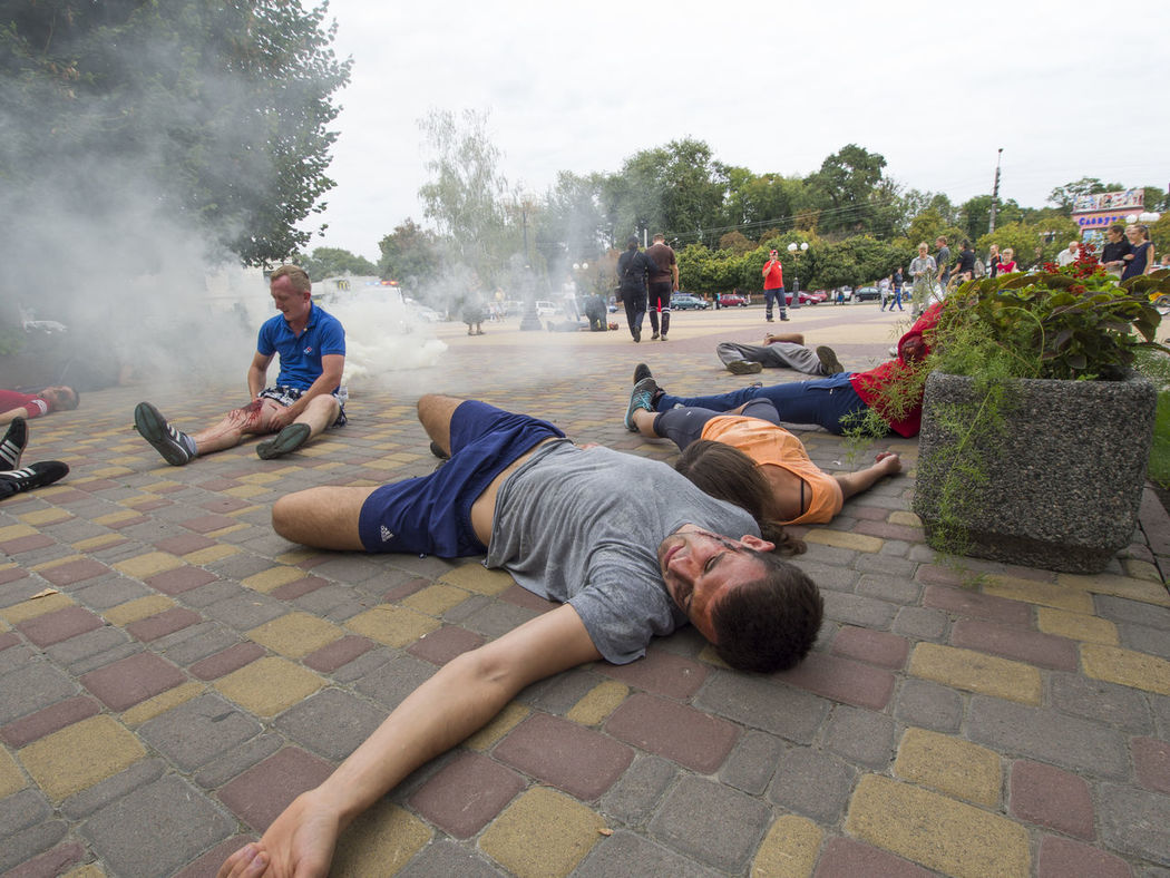 Red Cross held on Saturday, September 10, 2016, in Borispol, Ukraine training to rescue the wounded, the victims of the terrorist attacks. Attacks Casual Clothing Day Doctor  Full Length Homelessness  Incidental People Leisure Activity Lifestyles Men Park Park - Man Made Space Paving Stone Person Police Red Cross Relaxation Rescue Sitting Sky Terrorist Training Tree Victims Wounded