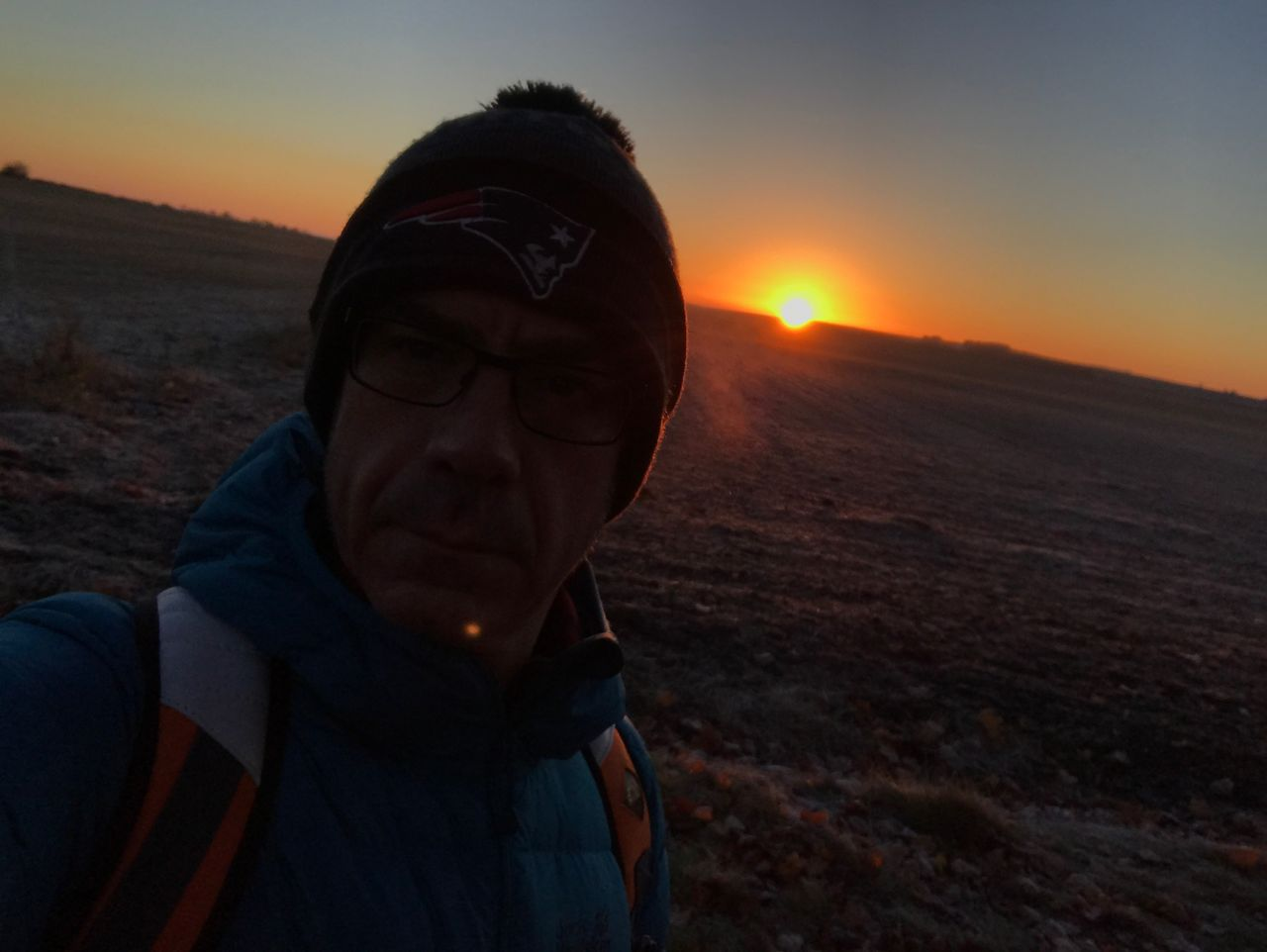 sunset, real people, one person, leisure activity, nature, outdoors, landscape, lifestyles, headshot, scenics, beauty in nature, sun, sky, adventure, hiking, mountain, standing, vacations, winter, warm clothing, day, close-up, young adult, people