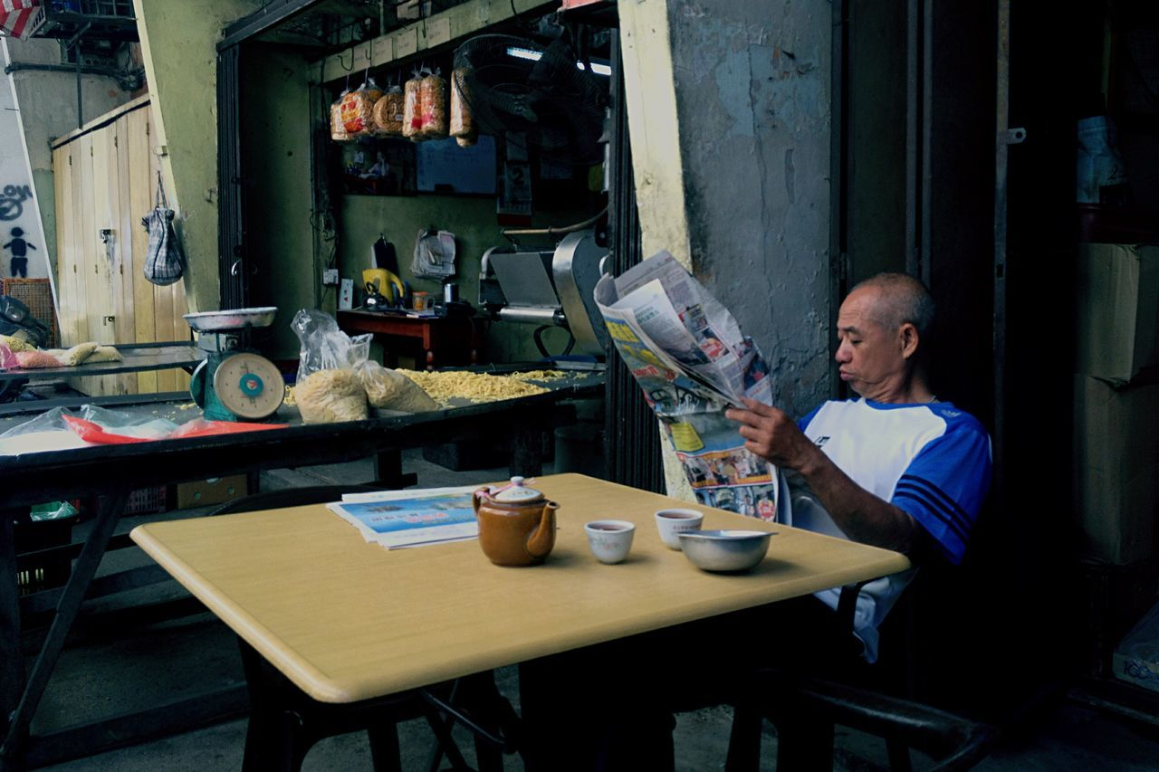 A man read a newspaper at wet market in Kuala Lumpur. Photo by Samsul Said Still Life Asiapictures Malaysia