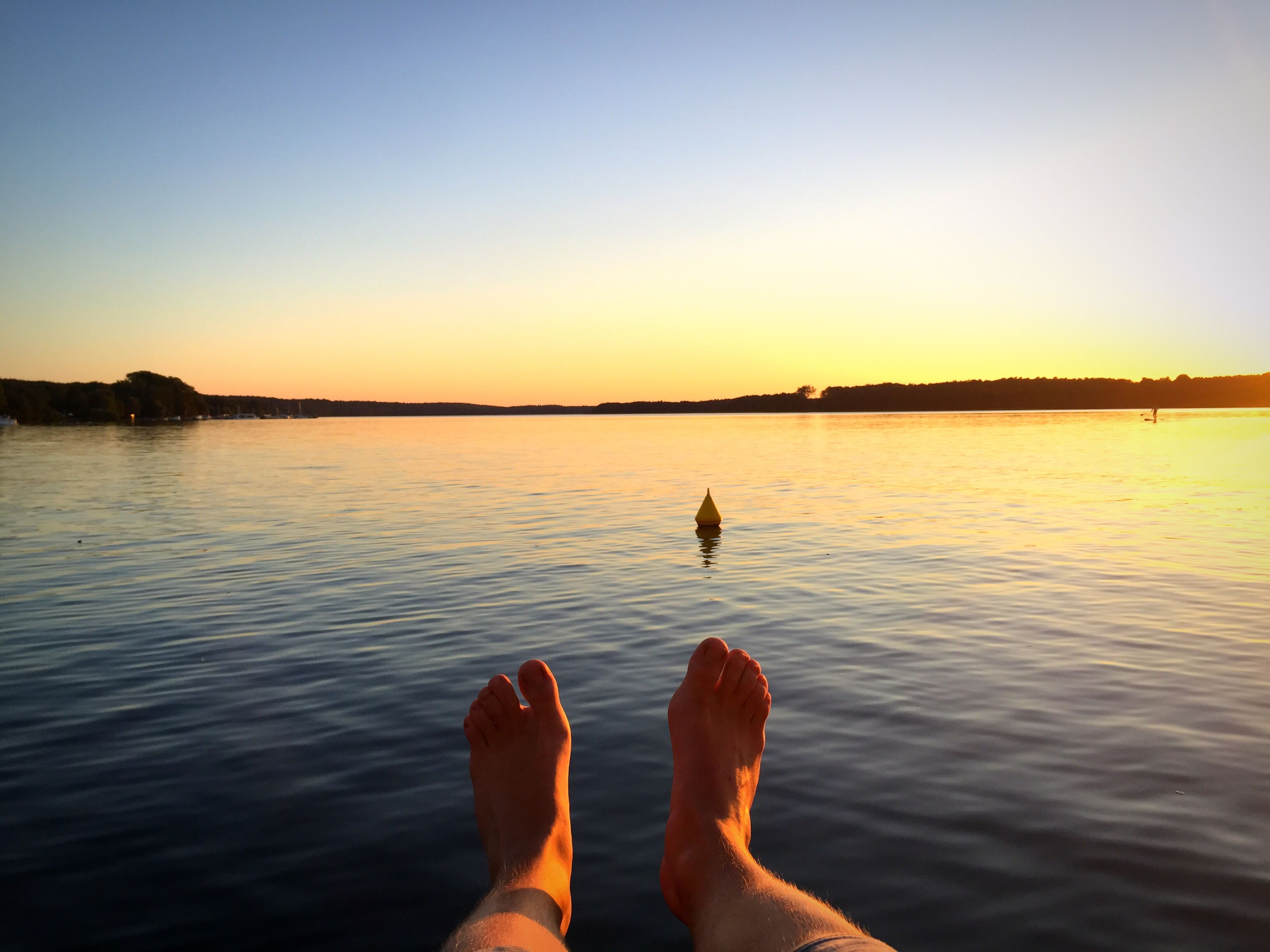 water, low section, person, sunset, personal perspective, rippled, barefoot, lake, copy space, relaxation, clear sky, tranquility, orange color, calm, vacations, tranquil scene, idyllic, scenics, solitude, sea, nature, beauty in nature, human foot, waterfront, outdoors, blue, summer, ocean, escapism, weekend activities, remote
