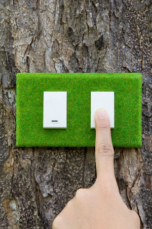 eco switch,save energy concept Earth Hour Eco Power Switch Adult Blank Close-up Day Eco Energy Eco Friendly Electric Light Energy Green Color Holding Human Body Part Human Finger Human Hand Nature One Person Outdoors Paper People Textured  Tree Tree Trunk