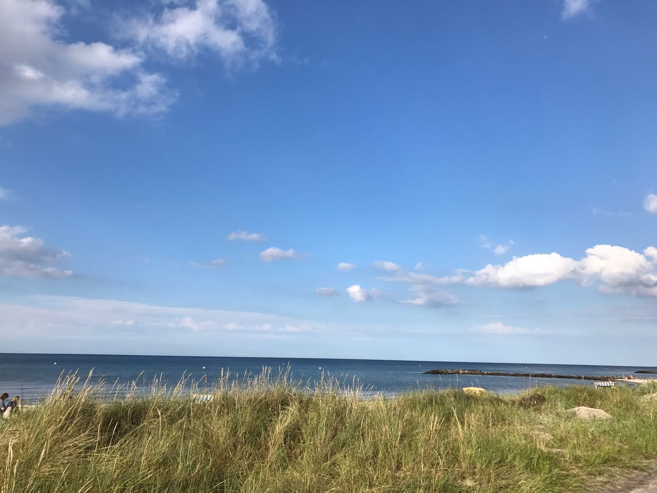 sea, horizon over water, tranquil scene, nature, scenics, grass, water, beach, tranquility, beauty in nature, sky, outdoors, marram grass, day, cloud - sky, no people, blue, vacations, travel destinations, sunlight, growth