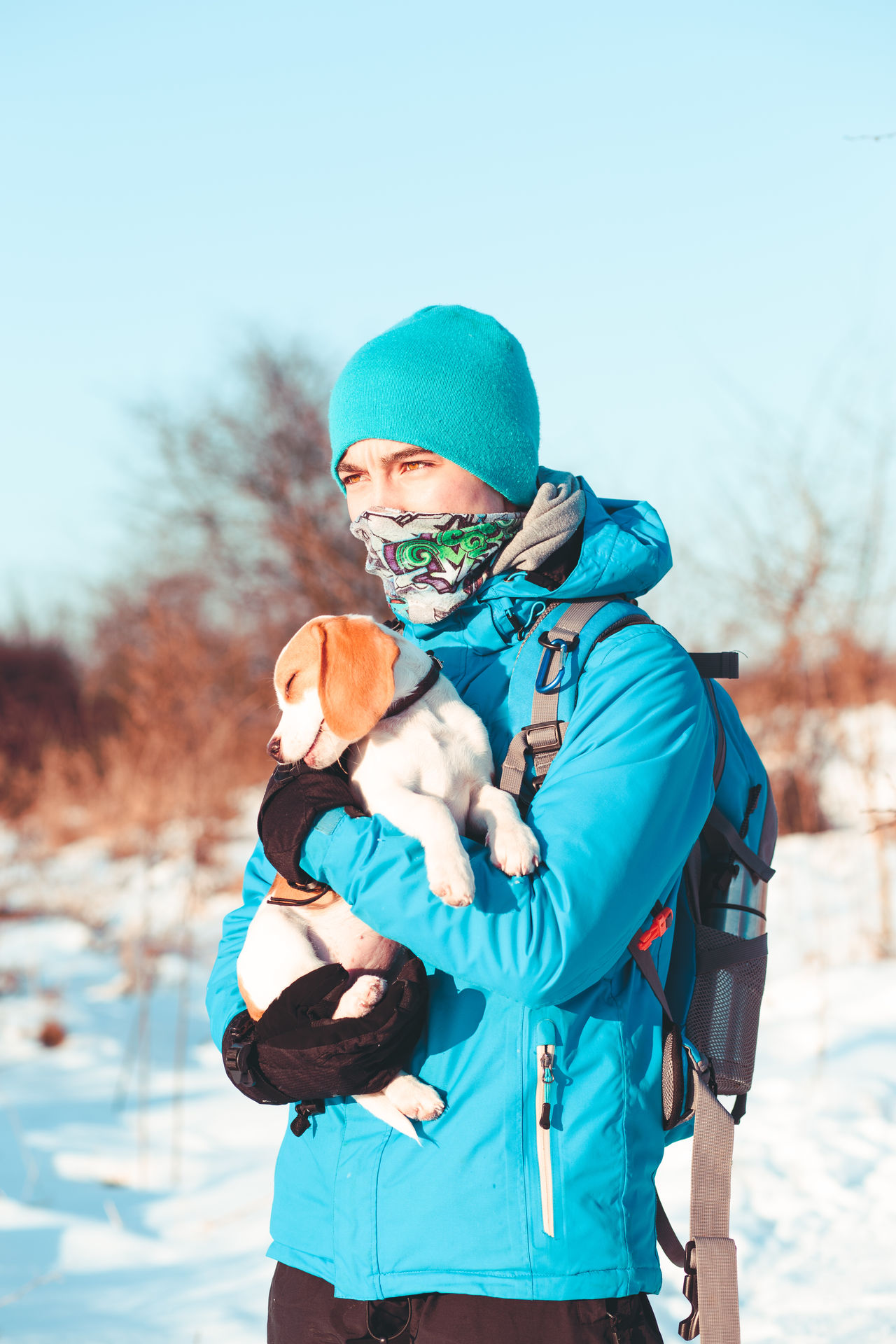 Boy holding the dog during the winter trip Active Activity Backpack Backpacking Bandana Boy Cold Day Dog Hike Hiker Journey Lifestyles Nature Outdoors People Person Pet Puppy Snow Teenager Trip Walk Winter Wintertime