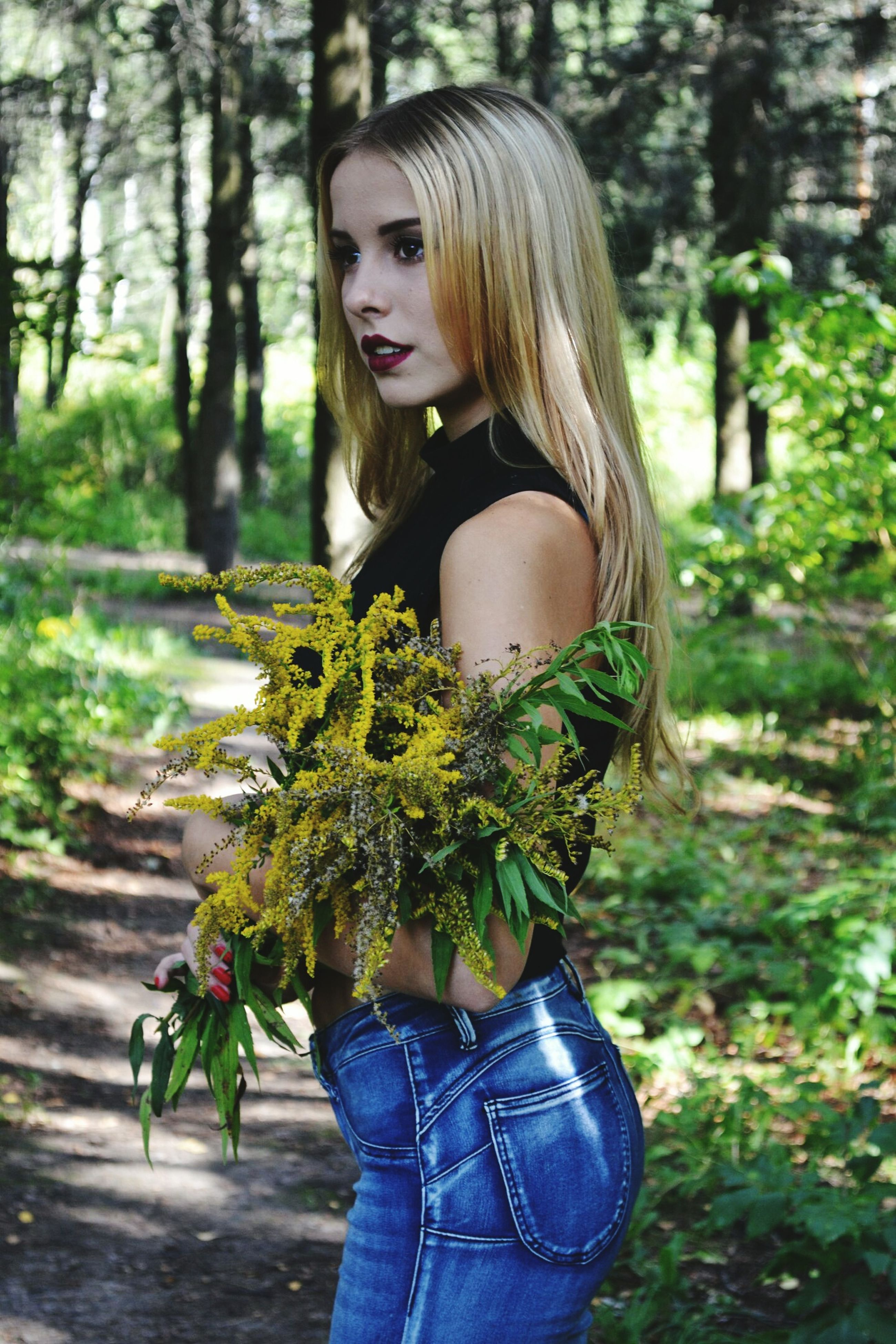 young women, young adult, tree, long hair, standing, leisure activity, forest, lifestyles, focus on foreground, casual clothing, beauty, front view, person, holding, woodland, day, leaves, nature, outdoors, freshness, beautiful people