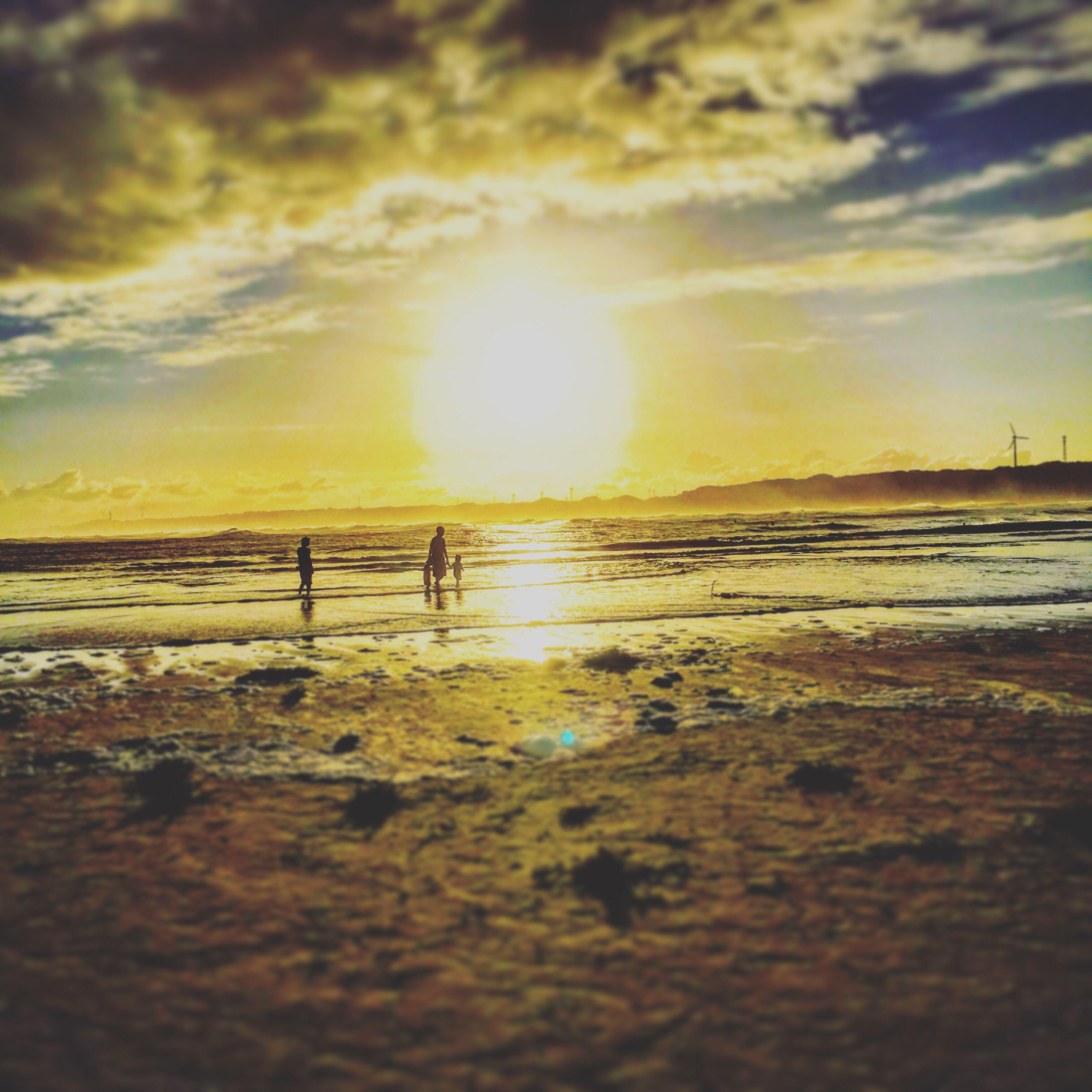 sunset, beach, sea, sun, vacations, water, scenics, tranquil scene, sand, tranquility, shore, tourism, walking, tide, coastline, majestic, idyllic, beauty in nature, calm, sky, travel destinations, reflection, tourist, nature, surface level, cloud - sky, coastal feature, sunbeam