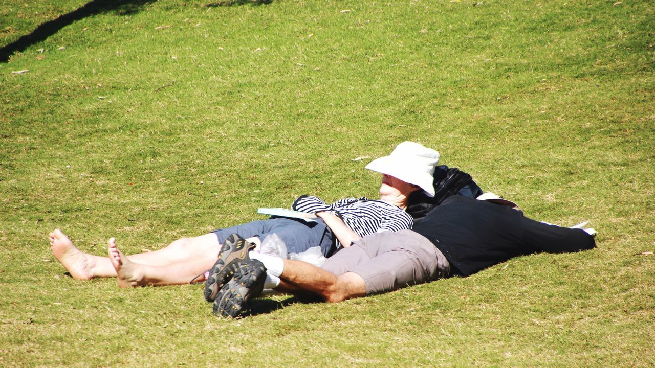 grass, real people, field, leisure activity, full length, lying down, lying on back, one person, day, relaxation, animal themes, lifestyles, outdoors, mammal, pets, nature, domestic animals