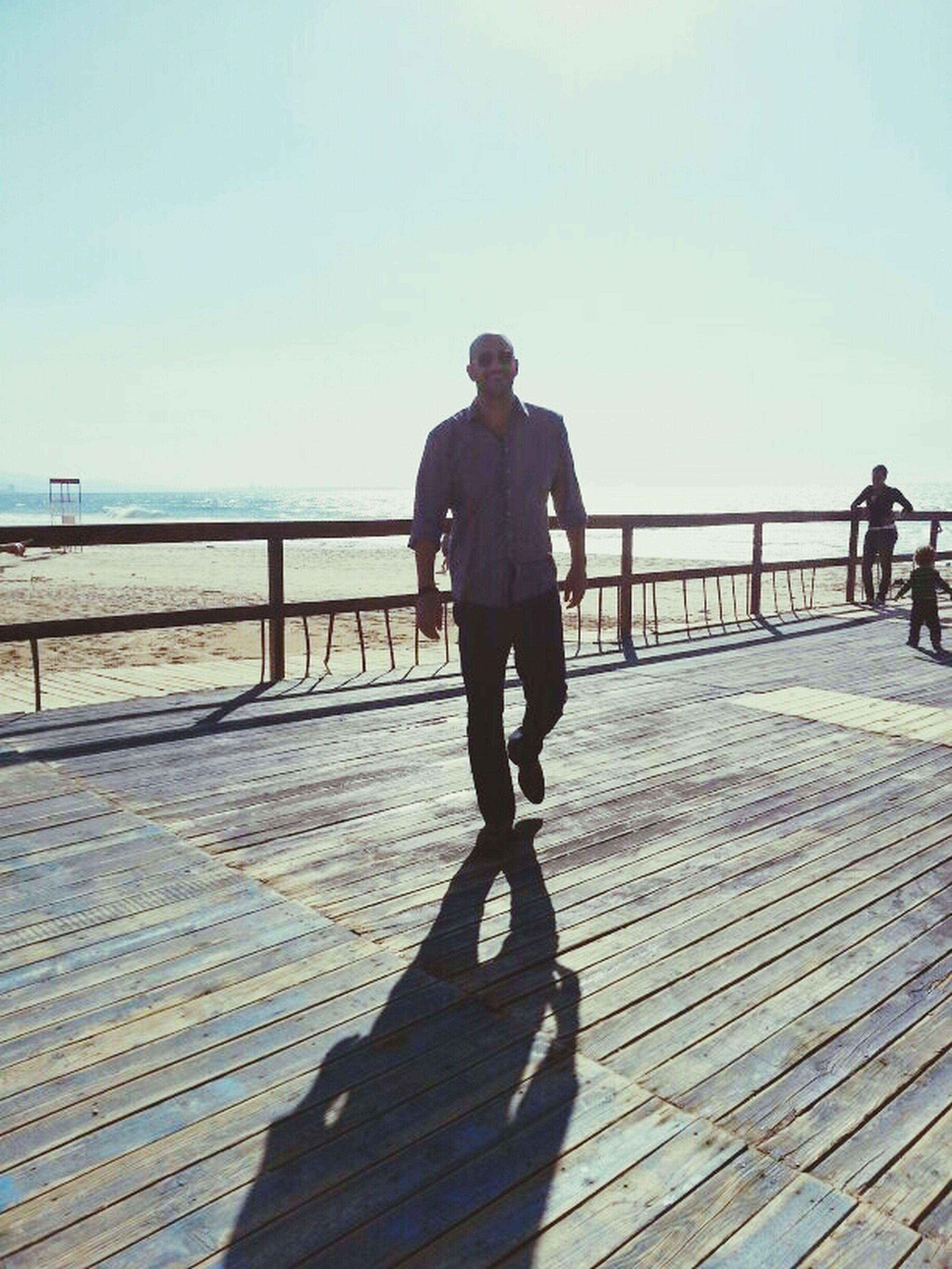 clear sky, full length, lifestyles, leisure activity, copy space, sea, railing, water, standing, rear view, pier, casual clothing, beach, walking, men, sunlight, person, outdoors