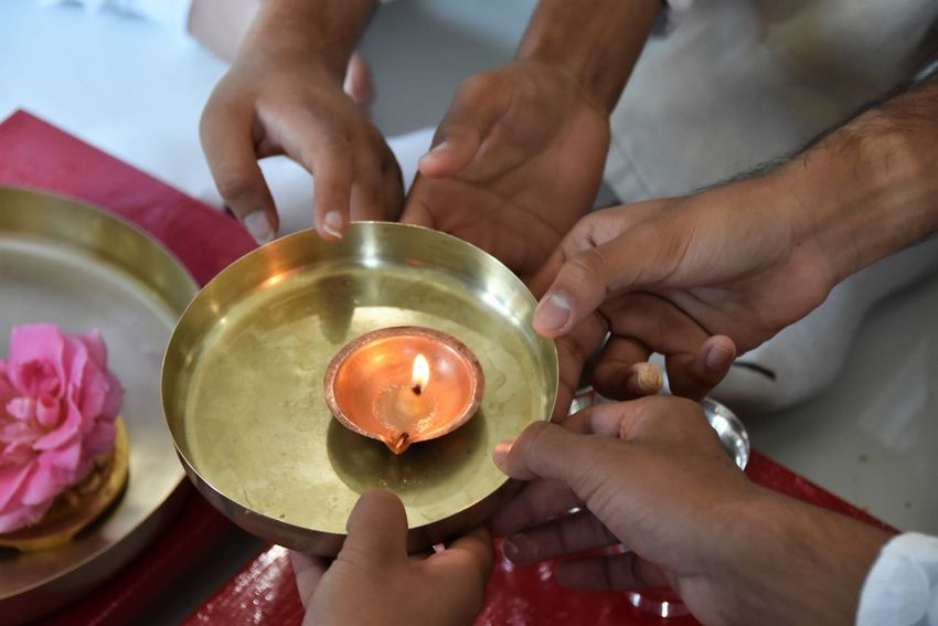 Close-up Day Flame Holding Human Body Part Human Hand Indoors  Jain Religion Lamp Light Real People Religious  Religious Rituals. Spirituality Teamwork Togetherness